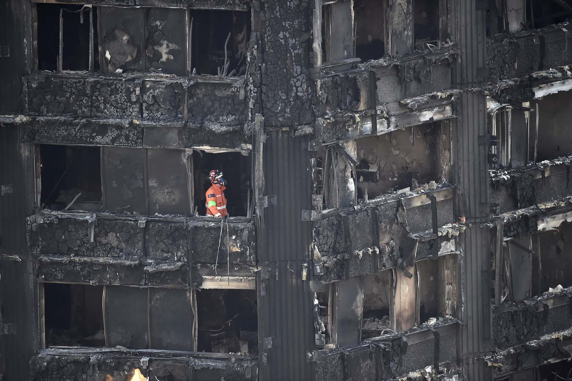 Un miembro de los servicios de emergencia trabaja dentro de la torre de apartamentos Grenfell en North Kensington, Londres