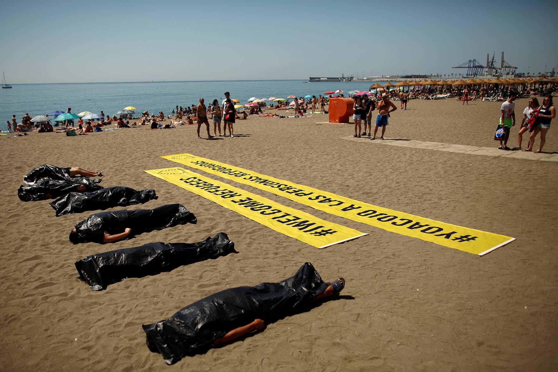 Para conmemorar el Día Mundial de los Refugiados, activistas de Amnistía Internacional participan en una actuación en Málaga que simula la muerte de inmigrantes en el Mar Mediterráneo