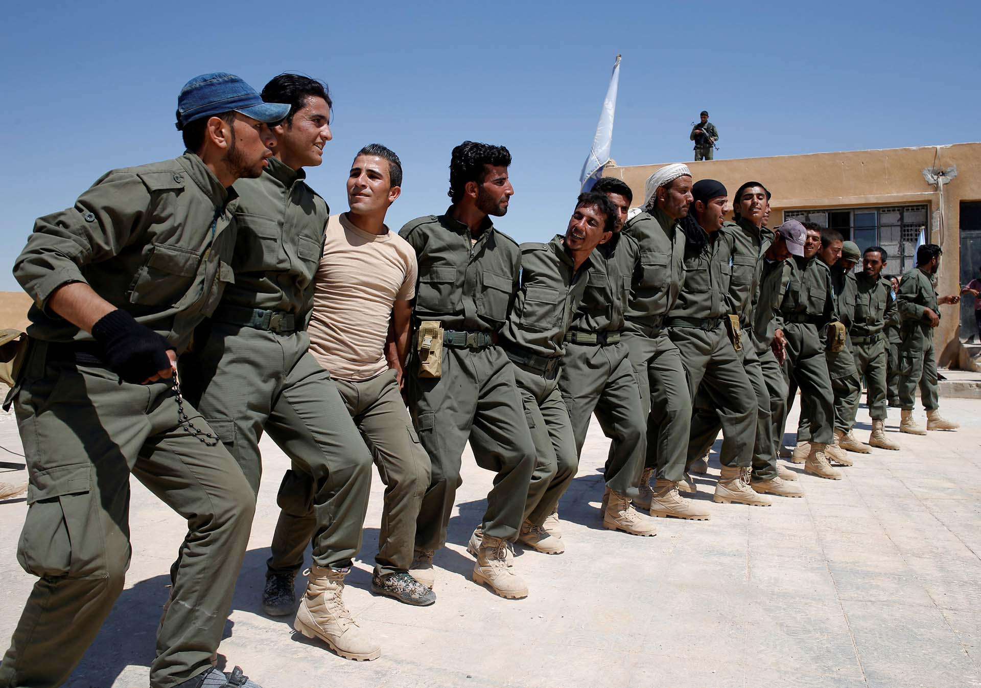 Los graduados de una fuerza de policía estadounidense, que esperan ser desplegados en Raqqa, bailan durante una ceremonia de egreso cerca del pueblo de Ain Issa, al norte de Raqqa, Siria