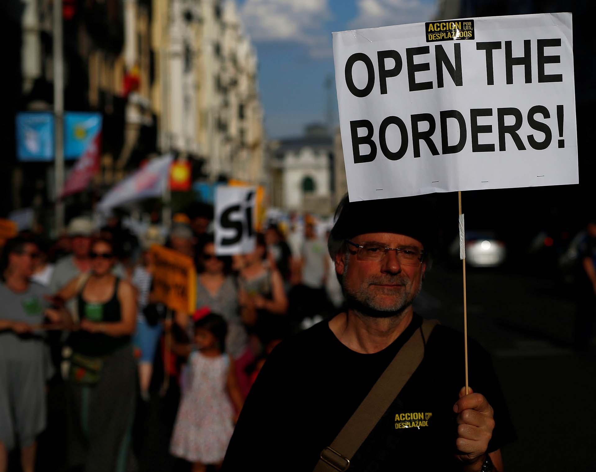 Un hombre marcha en Madrid pidiendo la apertura de las fronteras durante un acto por el Día Mundial del Refugiado
