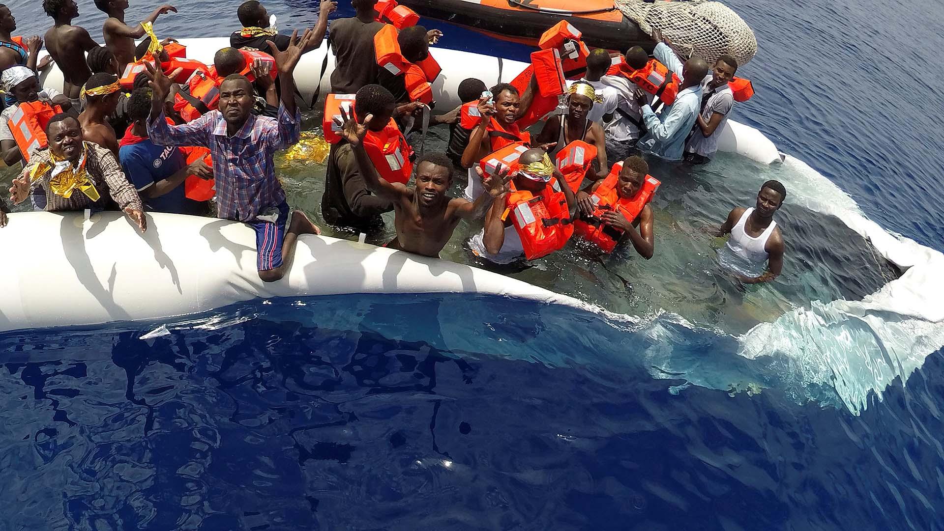 """Migrantes en un bote dañado son rescatados por el equipo de la ONG """"Save the Children"""" en el mar Mediterráneo frente a la costa de Libia"""