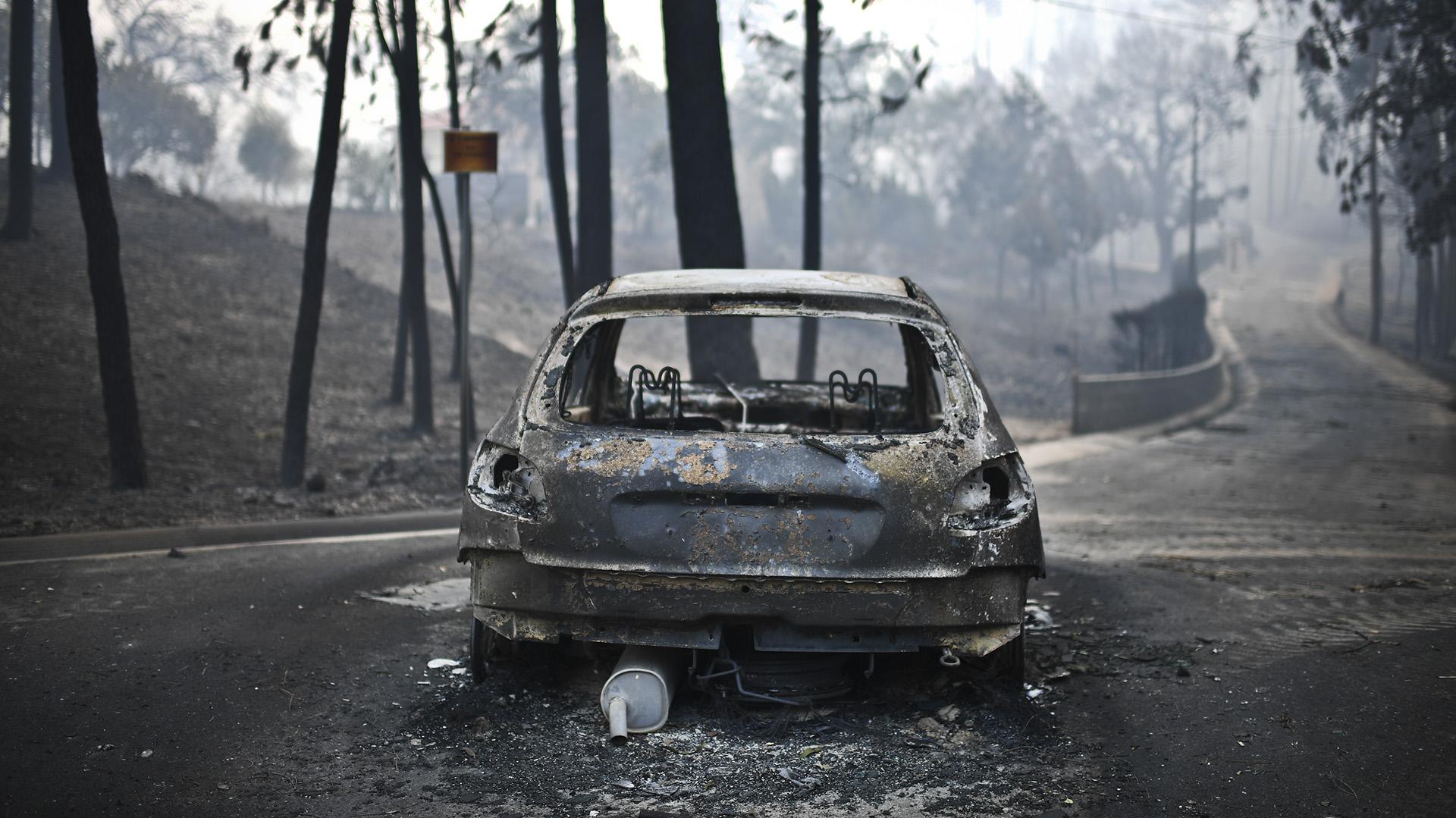 Un auto calcinado luego del incendio (AFP)