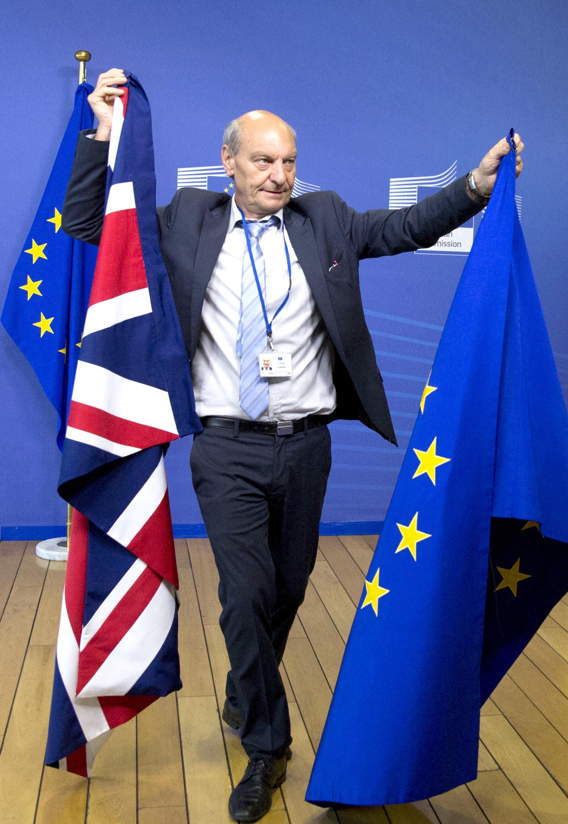 Un miembro del protocolo cambia las banderas de Gran Bretaña y de la Unión Europea antes del inicio de la discusión por el Brexit en Bruselas, Bélgica
