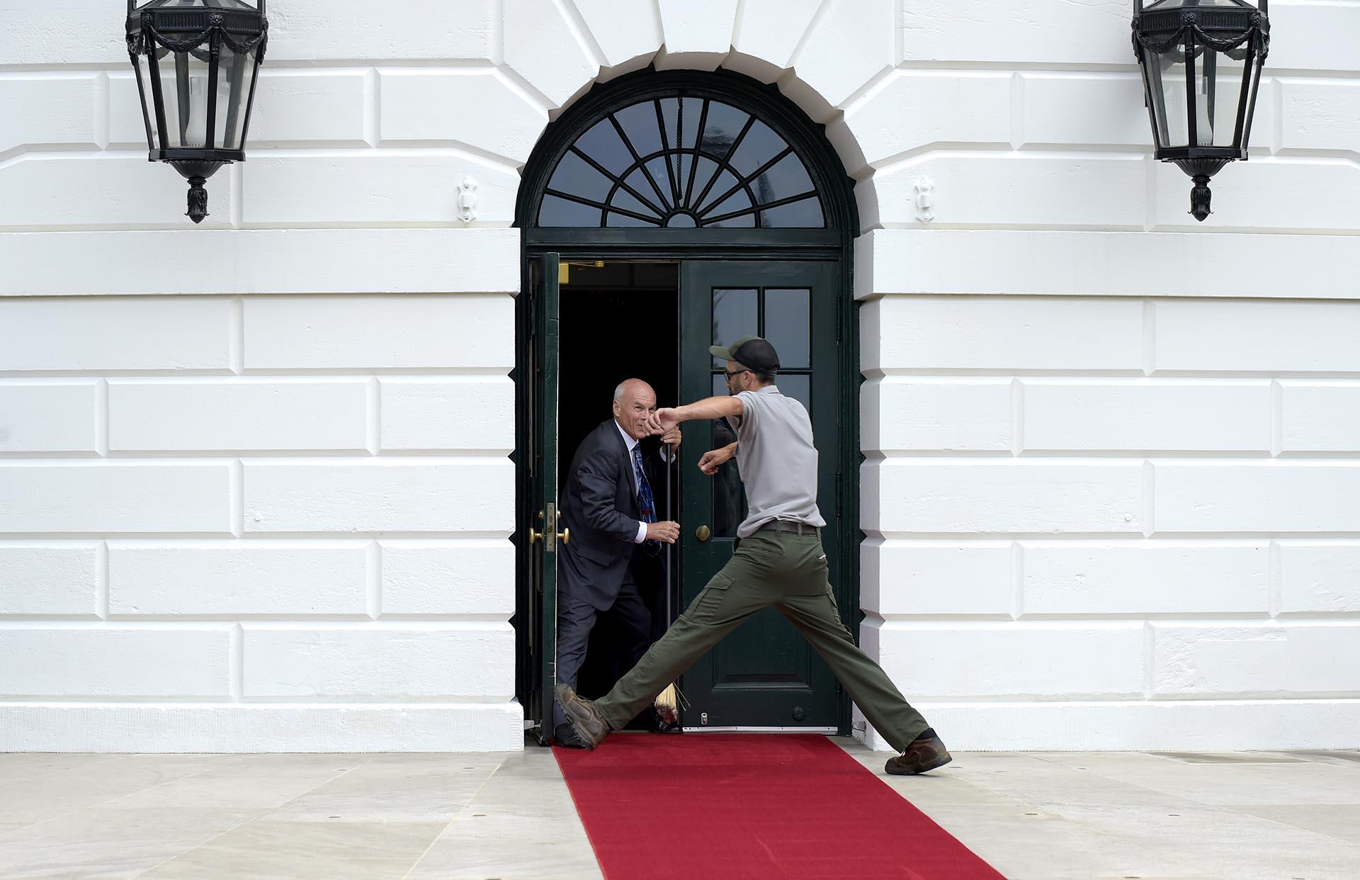 Un trabajador salta por encima de la alfombra roja en la Casa Blanca, antes del encuentroentre elpresidente de Estados Unidos, Donald Trump, y el máximo mandatario de Panamá, Juan Carlos Varela, en Washington, Estados Unidos
