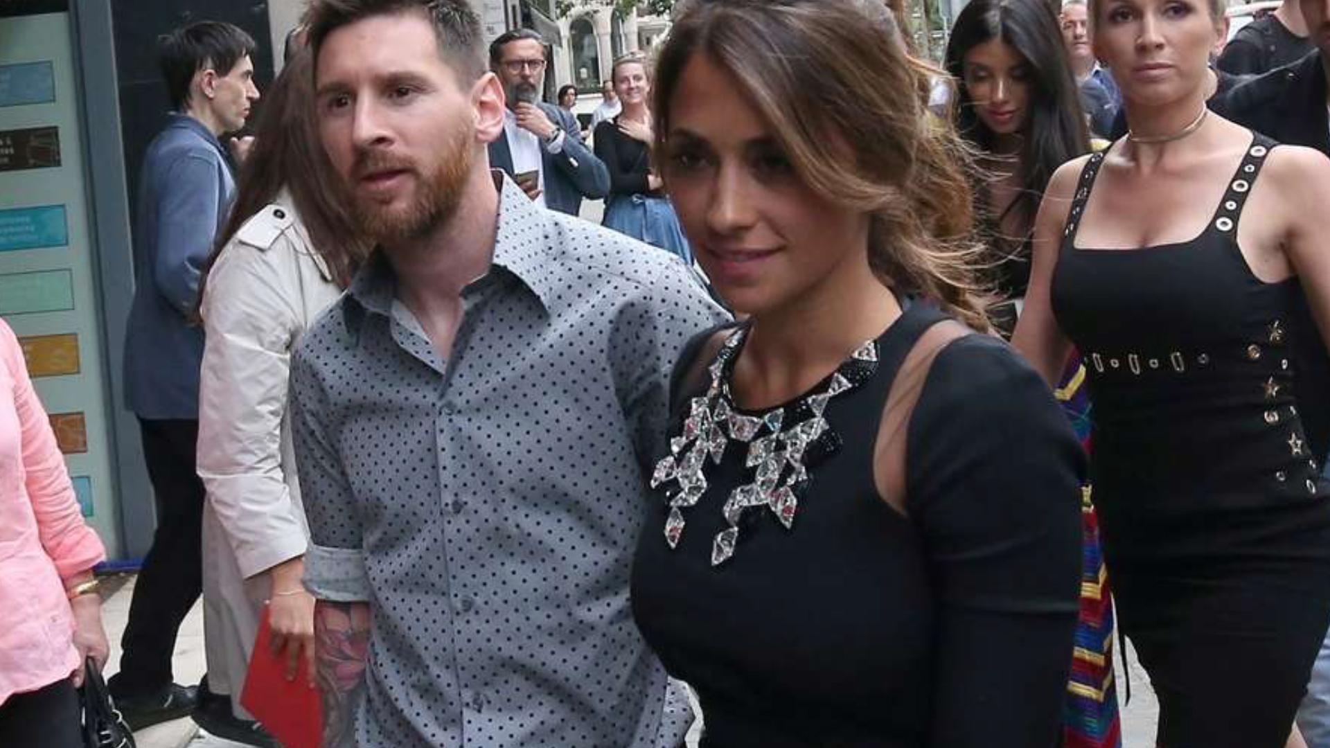 Con look relajado de camisa gris y lunares negros, Messi acompañó en su nuevo proyecto a su mujer, quien lució un vestido streech negro con piedras en el escote (2017 sarkany)