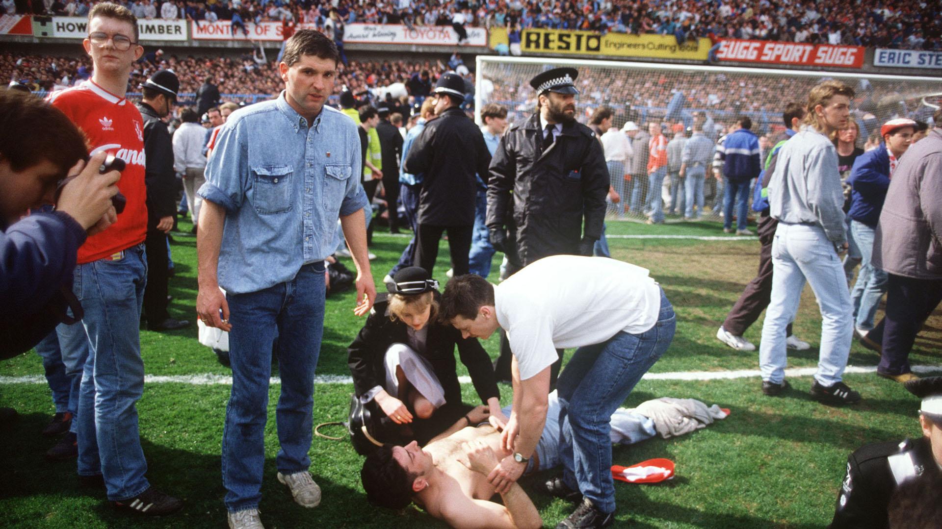 Los rescatistas ayudan a los fanáticos del fútbol en el estadio Hillsborough en Sheffield el 15 de abril de 1989, cuando 96simpatizantesdel Liverpool Football Club murieron aplastados y cientos resultaron heridos luego de que se derrumbaran las barandillas de apoyo durante una semifinal de la FA Cup entre Liverpool y Nottingham Forest