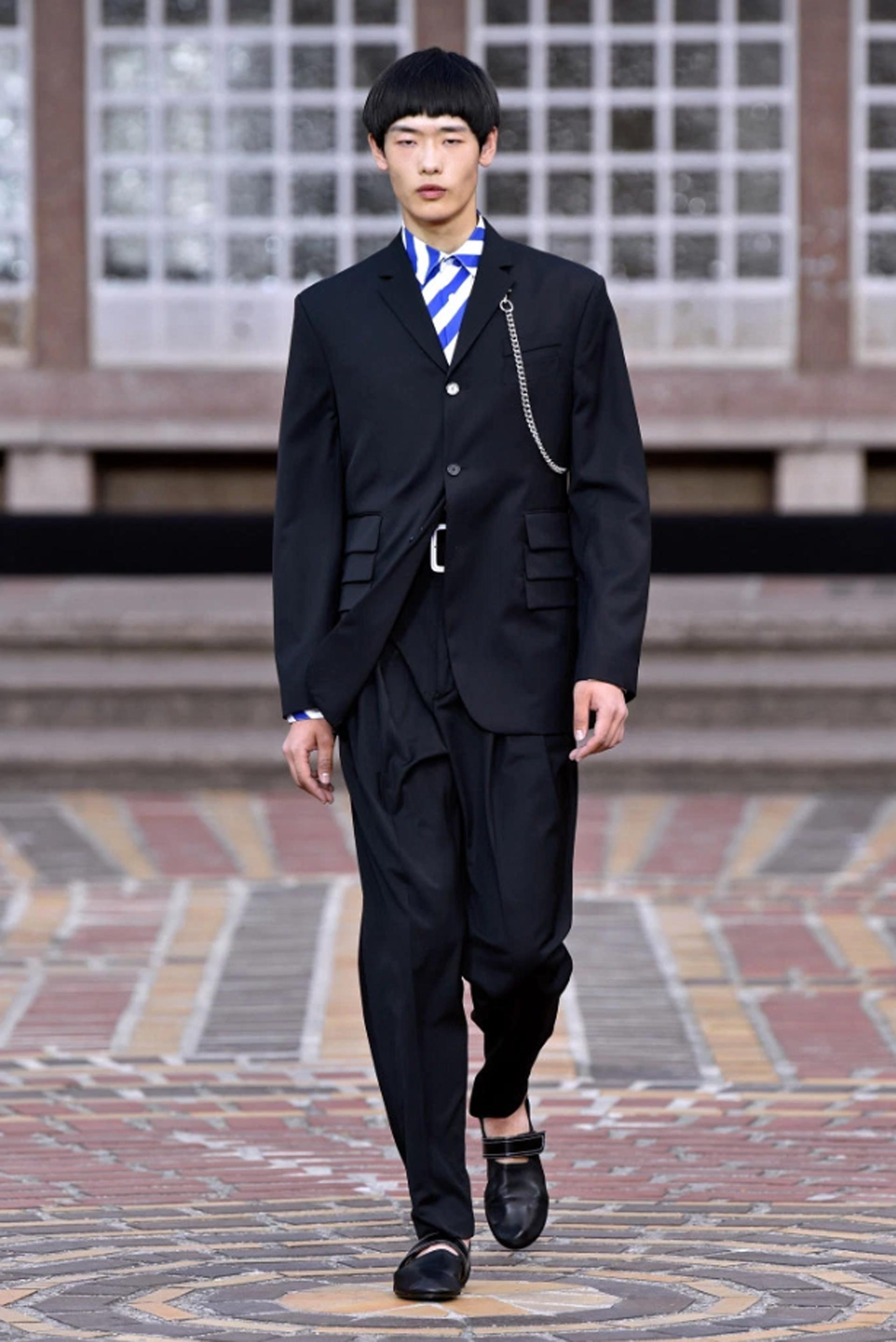 Un clásico smoking negro con un extravagante saco distinguido por tener unas pequeñas solapas y tres pliegues en los bolsillos delanteros. El detalle fue una cadena plateada. La camisa llamativa rayada en blanco y azul francia