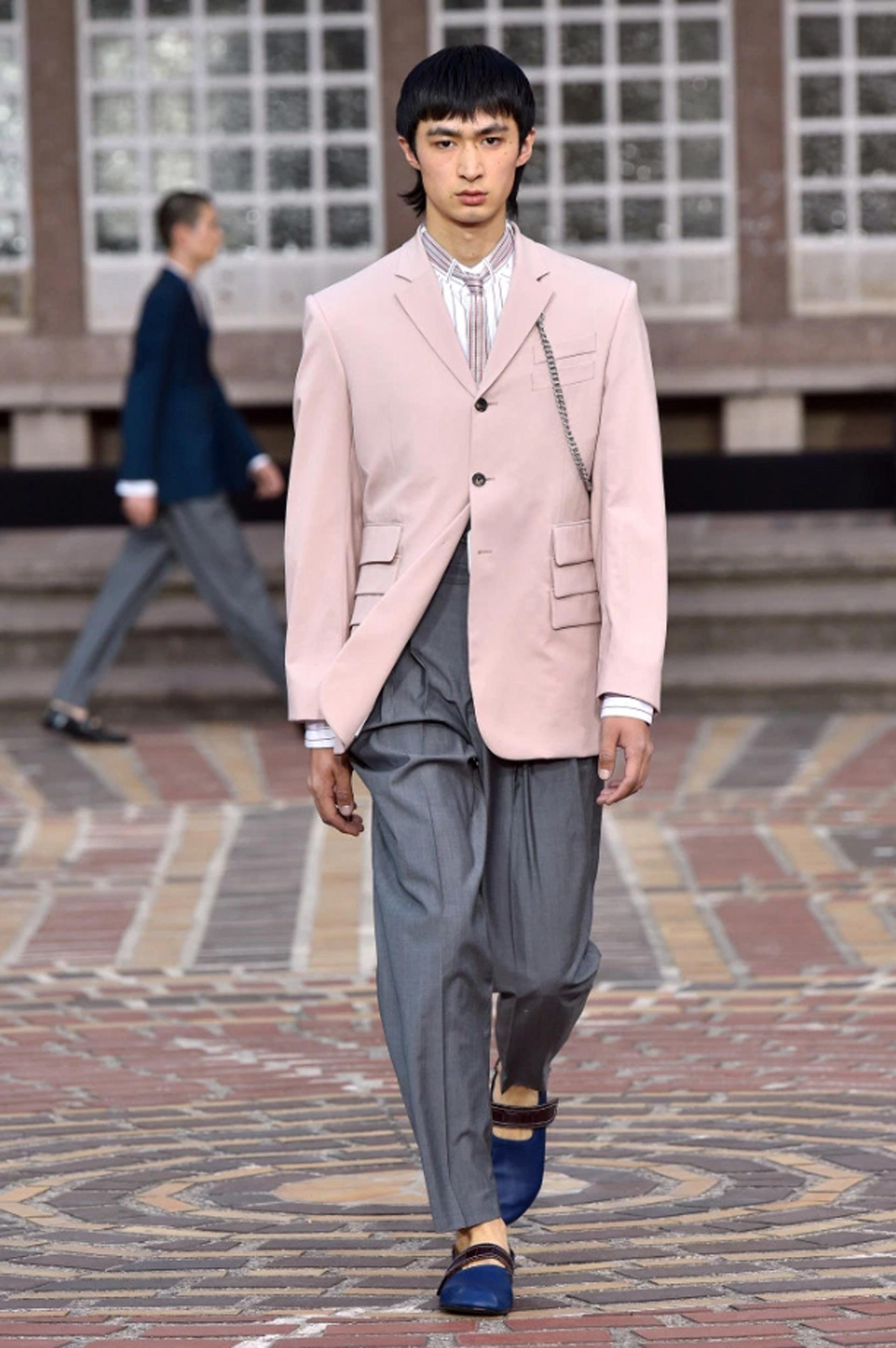 En combinación de un saco rosa pastel y un pantalón sastrero tiro alto en gris melange con camisa que simula tener una corbata como diseño