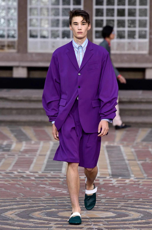 En violeta, la sastrería presentada por Kenzo por un saco oversize y bermudas junto a una camisa celeste rayada