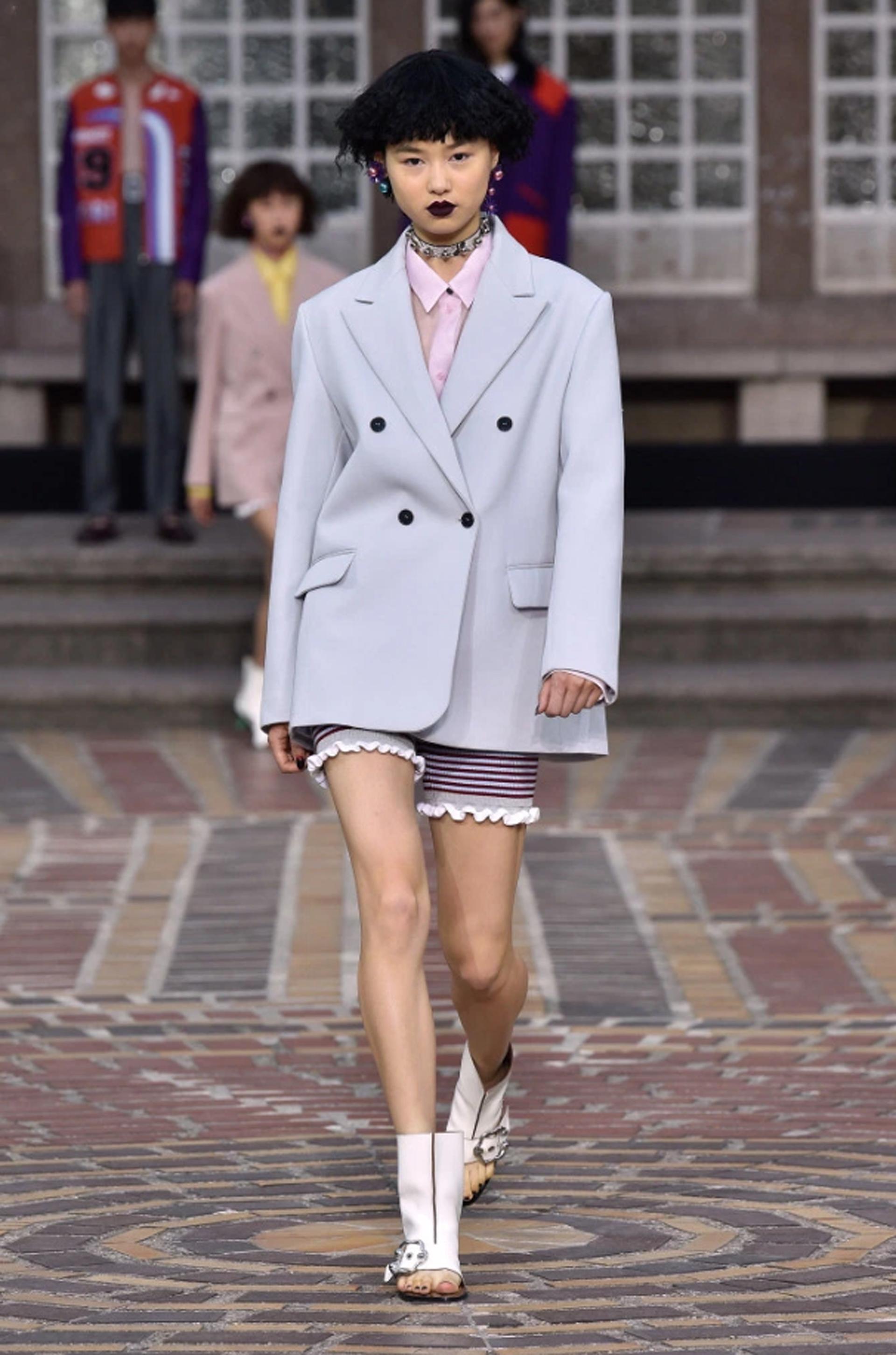 Linea XL de sastrería, saco gris con botones en negro y por debajo un short al cuerpo rayado en bordeaux combinando con camisa rosada. Chokers y aros fueron los accesorios elegidos