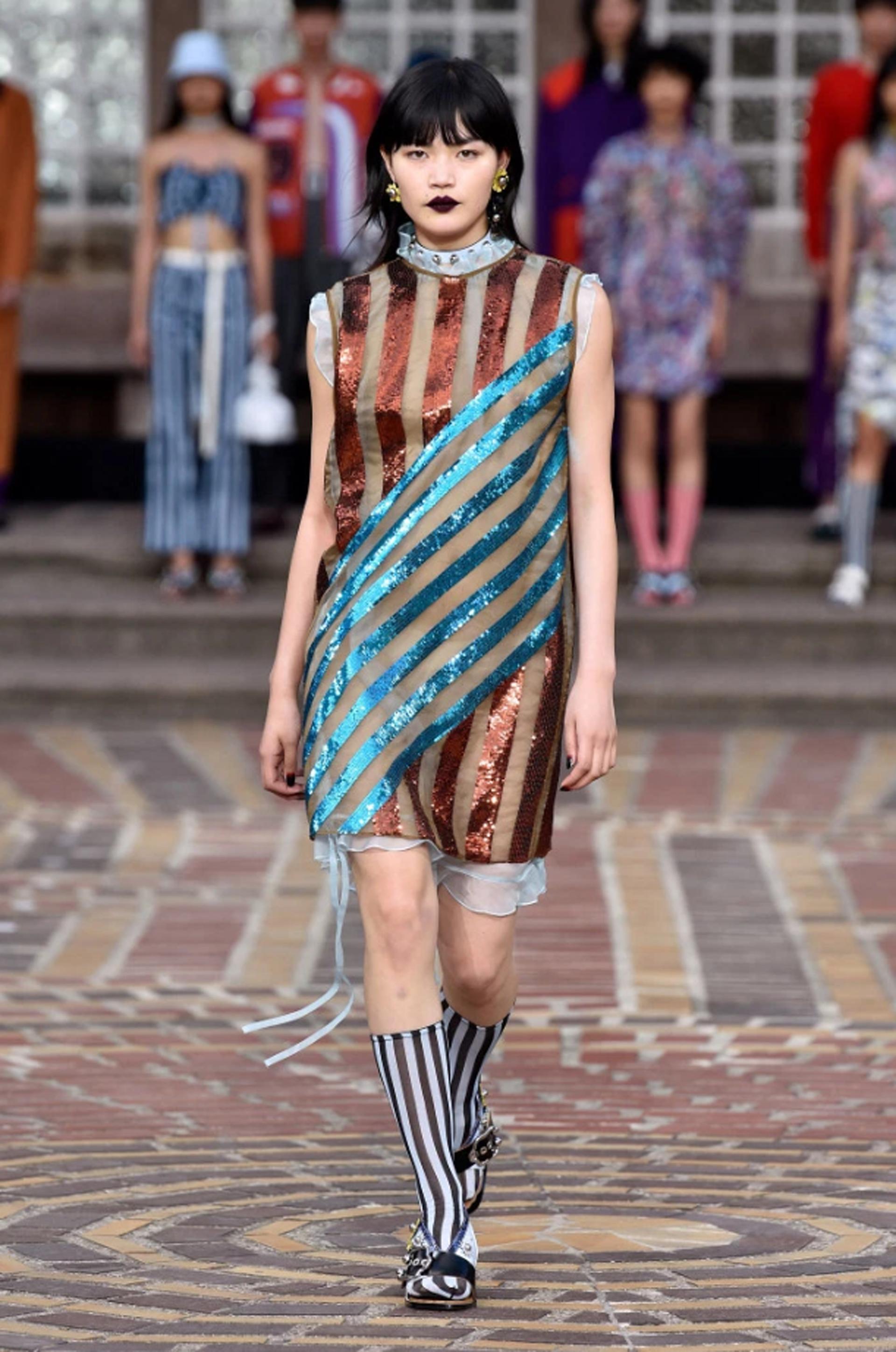 Rayas metalizadas y transparencias en un vestido corto sin mangas en bronce y turquesa. La combinación de medias y sandalias siguen siendo furor en la semana de la moda