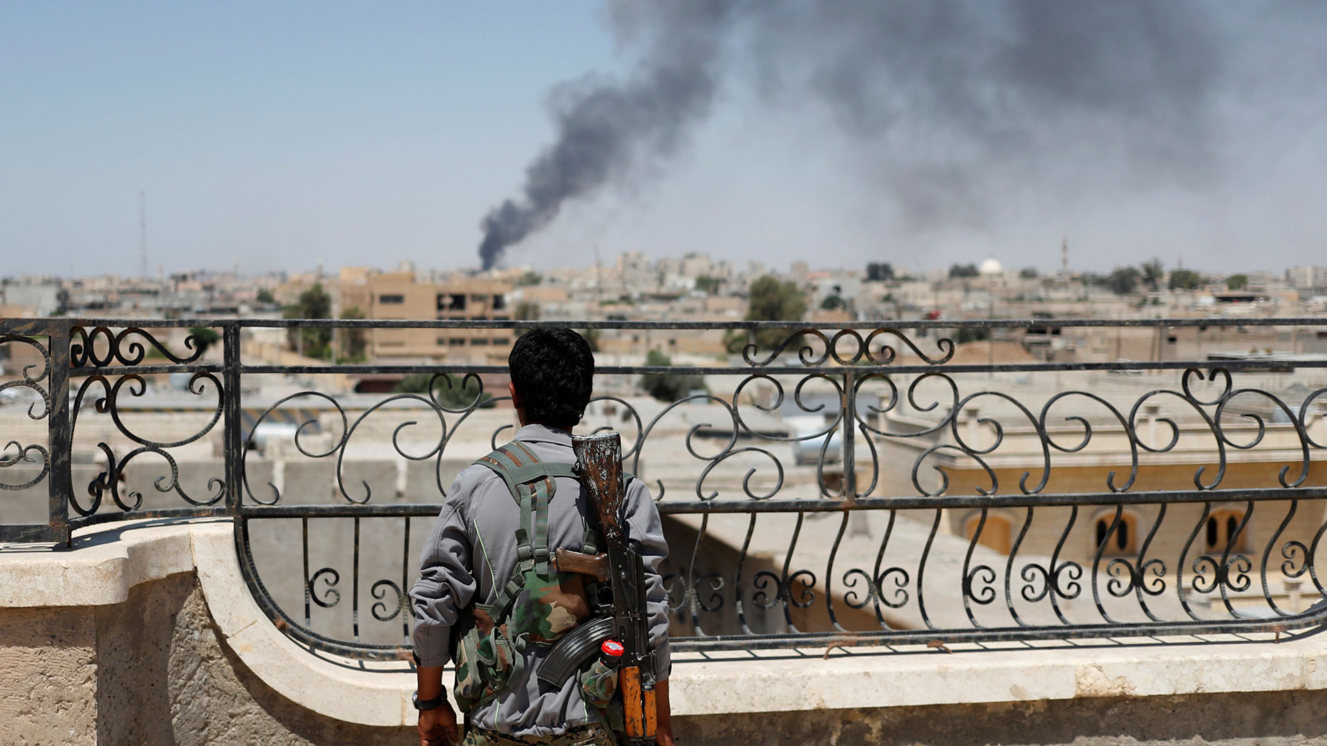 "Un combatiente kurdo observa a la ciudad de Raqqa, en Siria, poco antes de la ofensiva final sobre la que fuera capital del ""califato"" (Reuters)"