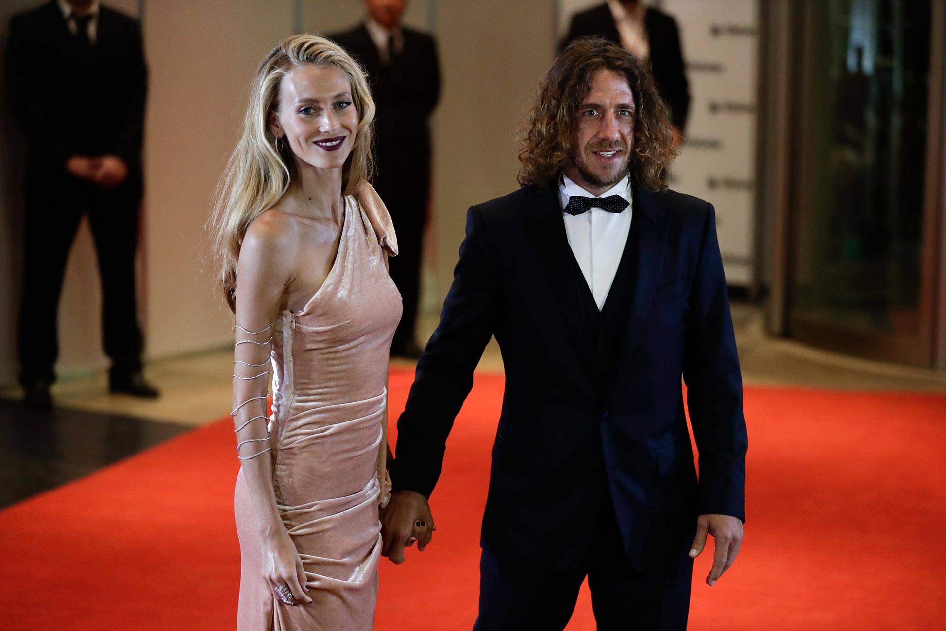 Carles Puyol en smoking y su mujer con un vestido de terciopelo nude con corte de un solo hombro. Su beauty look muy glamoroso