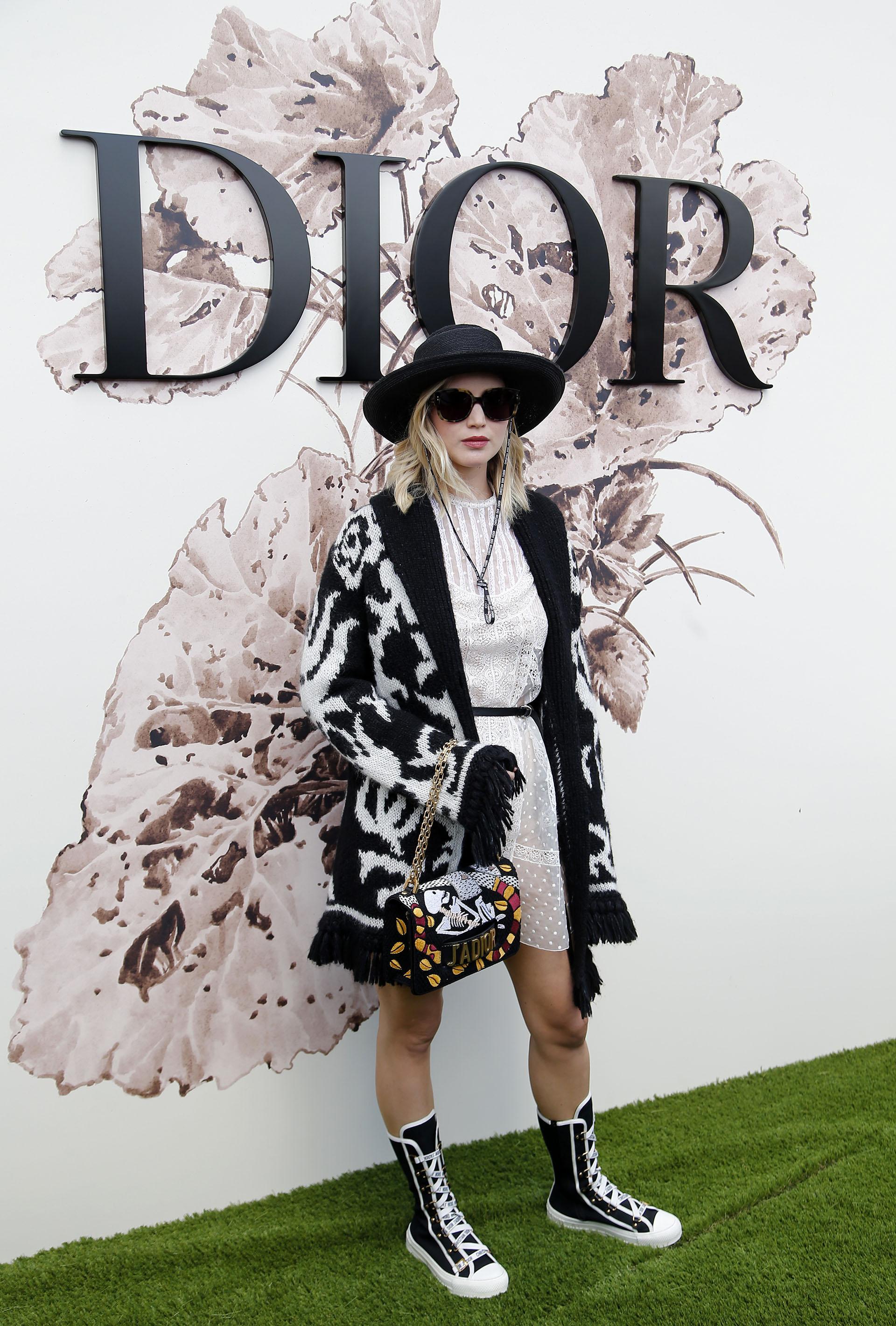La actrizJennifer Lawrence optó por un look más casual vestido blanco de encaje abrigo de lana y accesorios Dior (AP Photo/Thibault Camus)