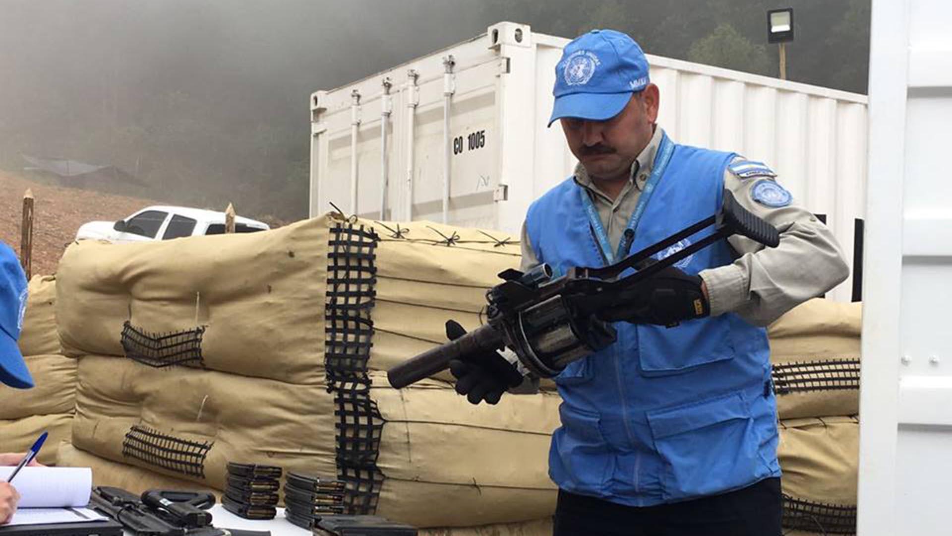 Un integrante del contingente argentino recibe las armas de las FARC