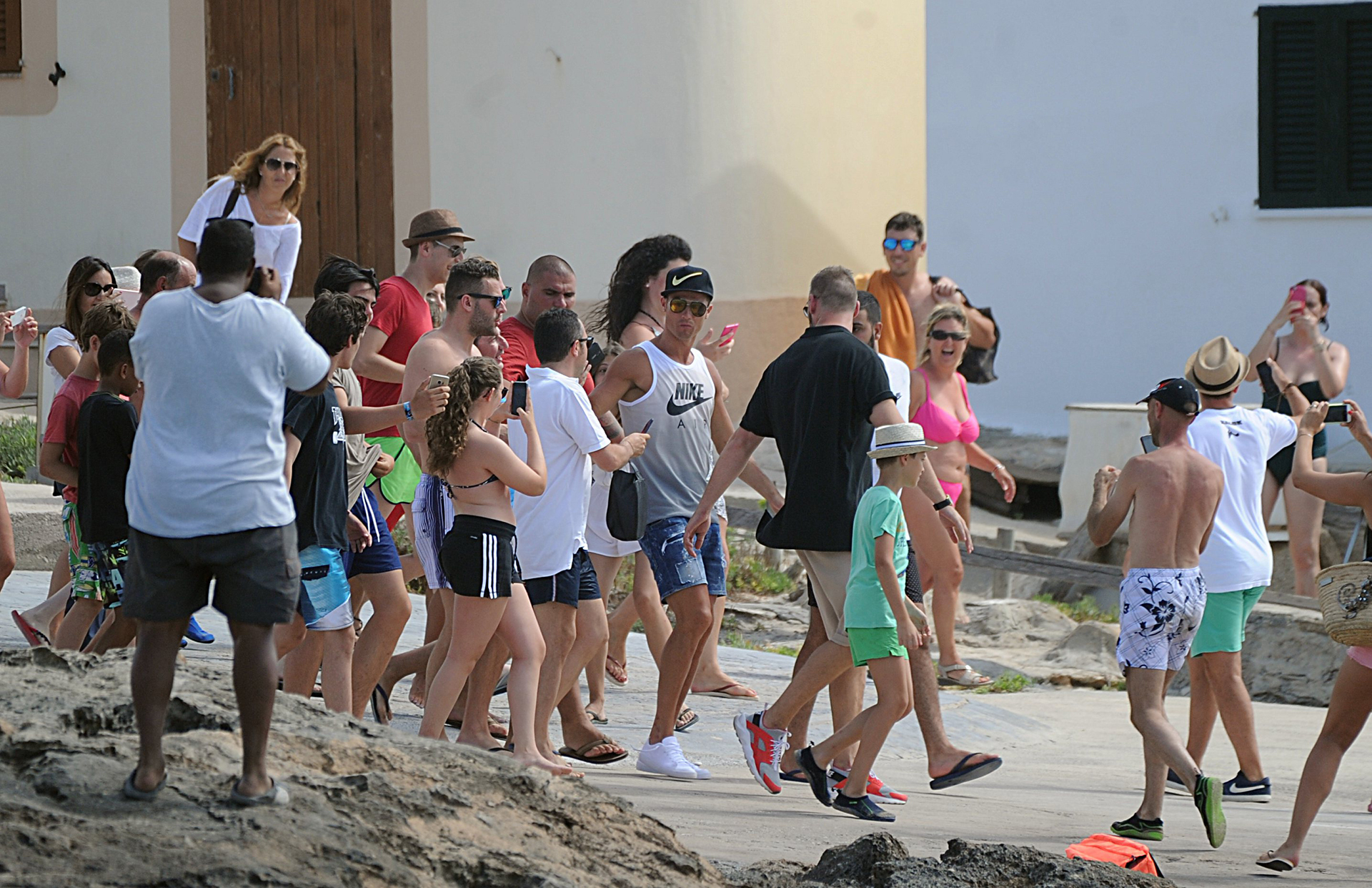 Parte del grupo que acompaña a Cristiano Ronaldo en Ibiza y algunos curiosos que, desesperados, apelaron a sus móviles para captar el momento de paso de la estrella