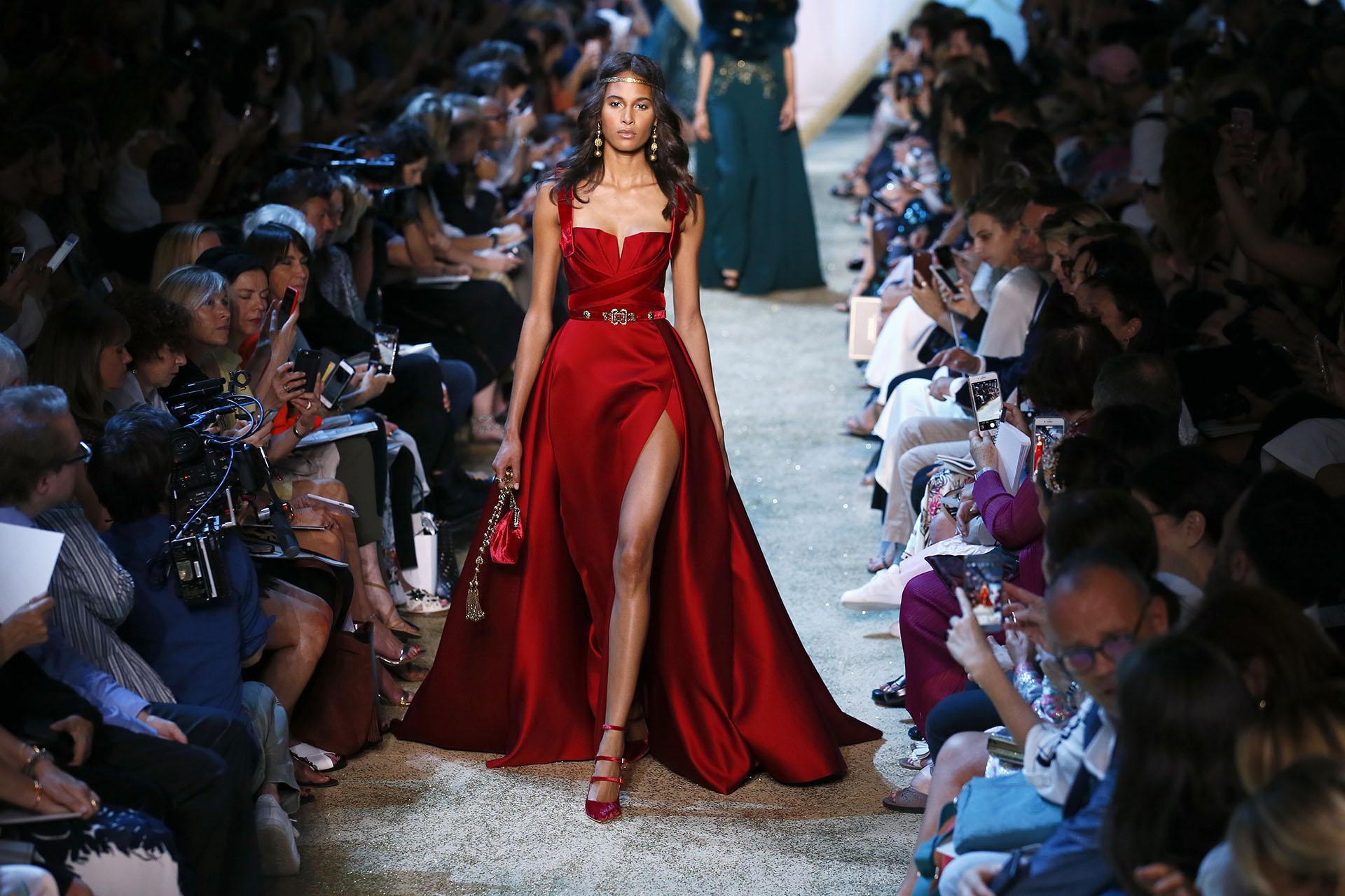 En rojo pasión, drapeado y siguiendo la tendencia del maxi tajo, acompañando el diseño con una mini cartera en velvet y sandalias con tiras a tono (AP Photo/Francois Mori)