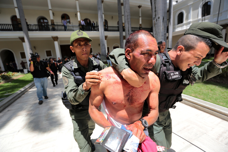 El testimonio gráifco de Llano mostró la sonrisa de un oficial al detener a uno de los sujetos que irrumpió en la Asamblea Nacional, que fue liberado poco después de los incidentes