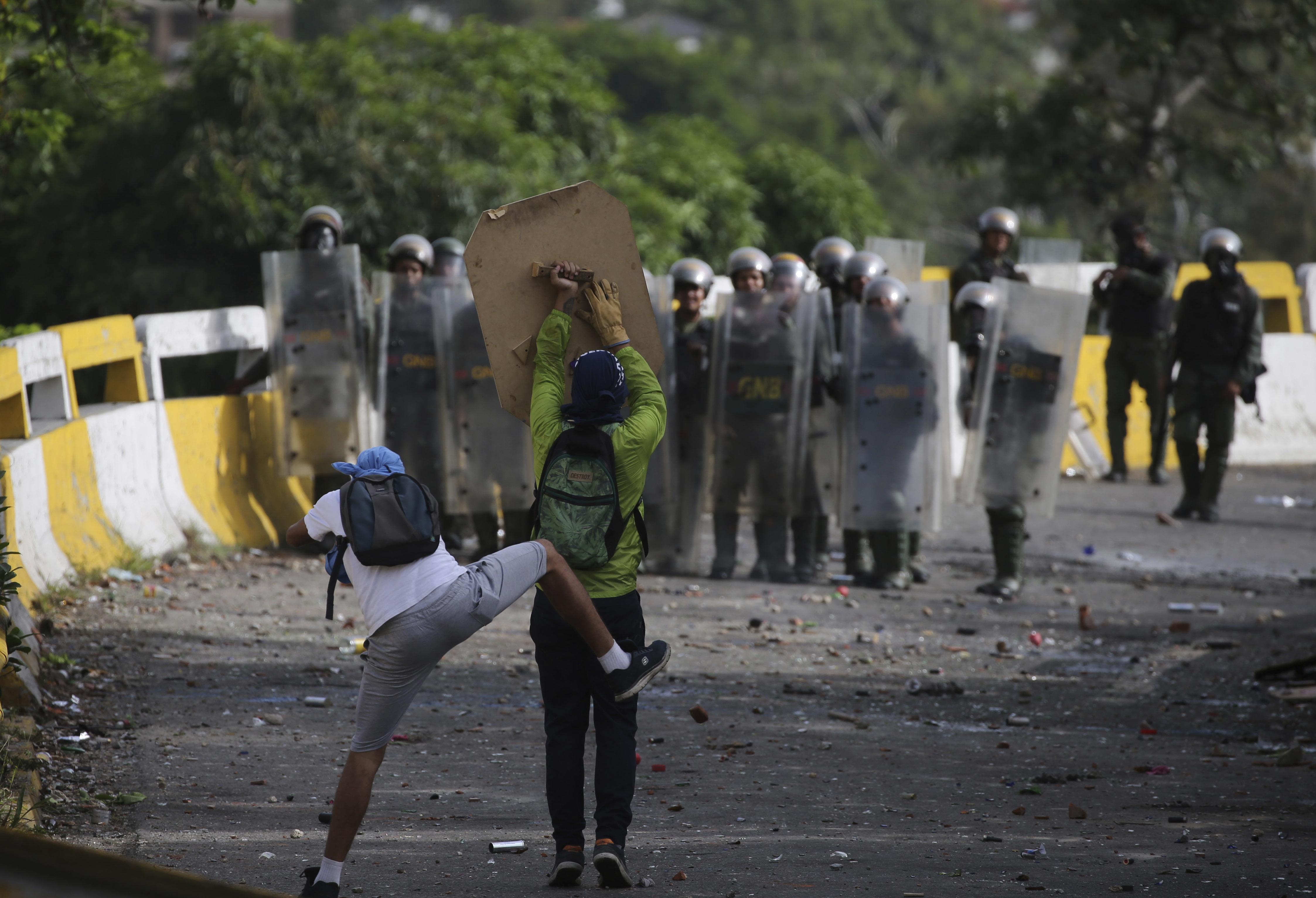 Los manifestantes intentan protegerse de los disparos de los oficiales chavistas