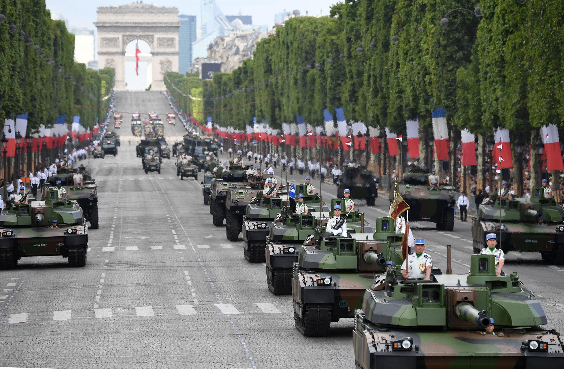 Miembros del Quinto Regimiento de los Dragones desfilan sobre tanques de guerra por el Día de la Bastilla (AFP)