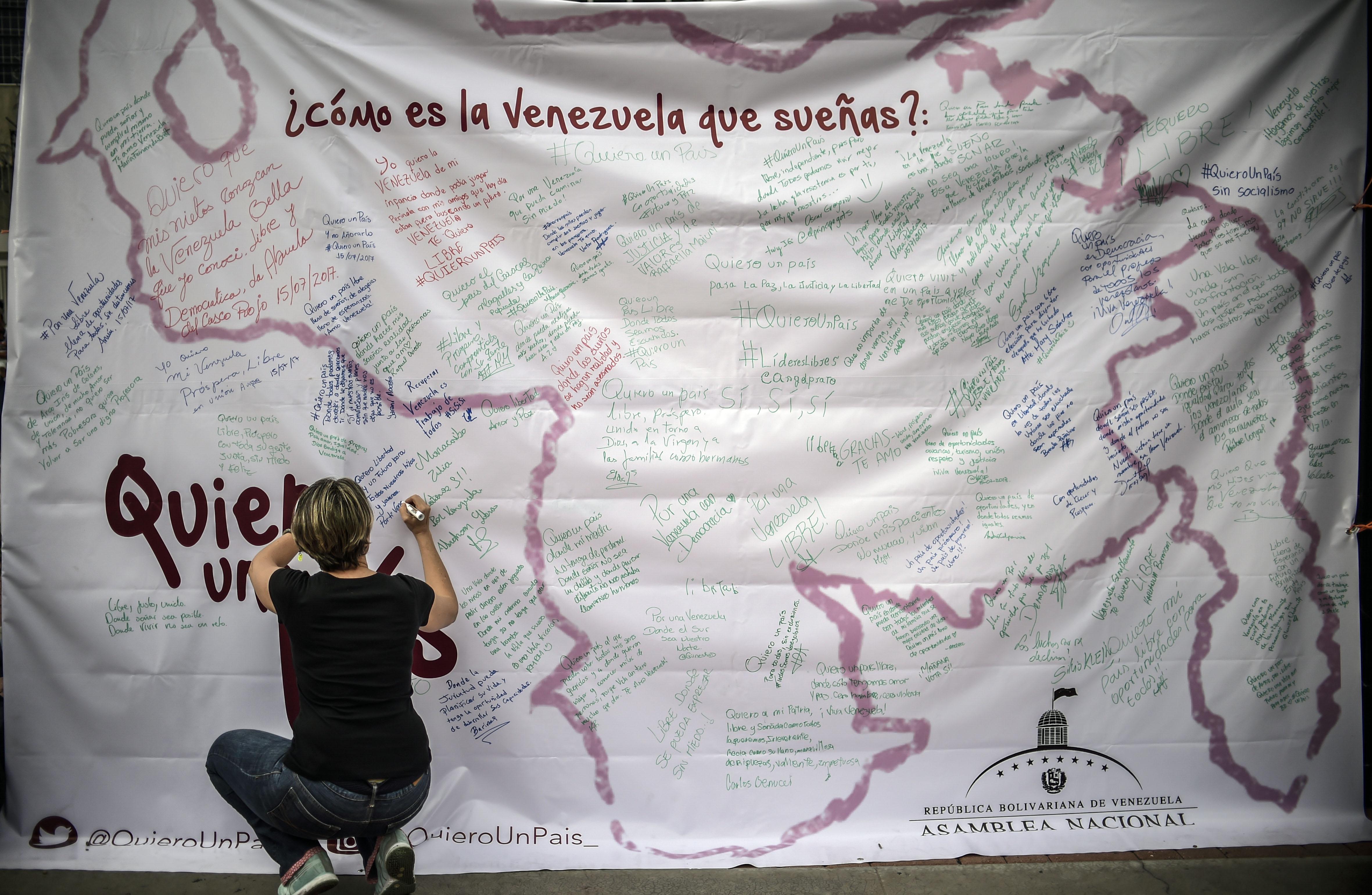 Una mujer escribe sobre un mapa de Venezuela en una manifestación a favor del plebiscito de este domingo. (AFP PHOTO / JUAN BARRETO)