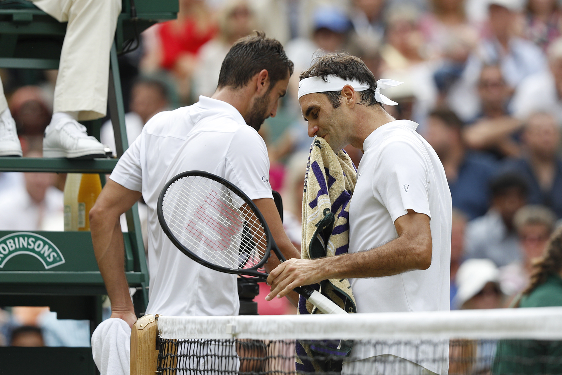 Switzerland's Roger Federer (R) passes Croatia's Marin Cilic as they swap ends during their men's singles final match on the last day of the 2017 Wimbledon Championships at The All England Lawn Tennis Club in Wimbledon, southwest London, on July 16, 2017. / AFP PHOTO / Adrian DENNIS / RESTRICTED TO EDITORIAL USE