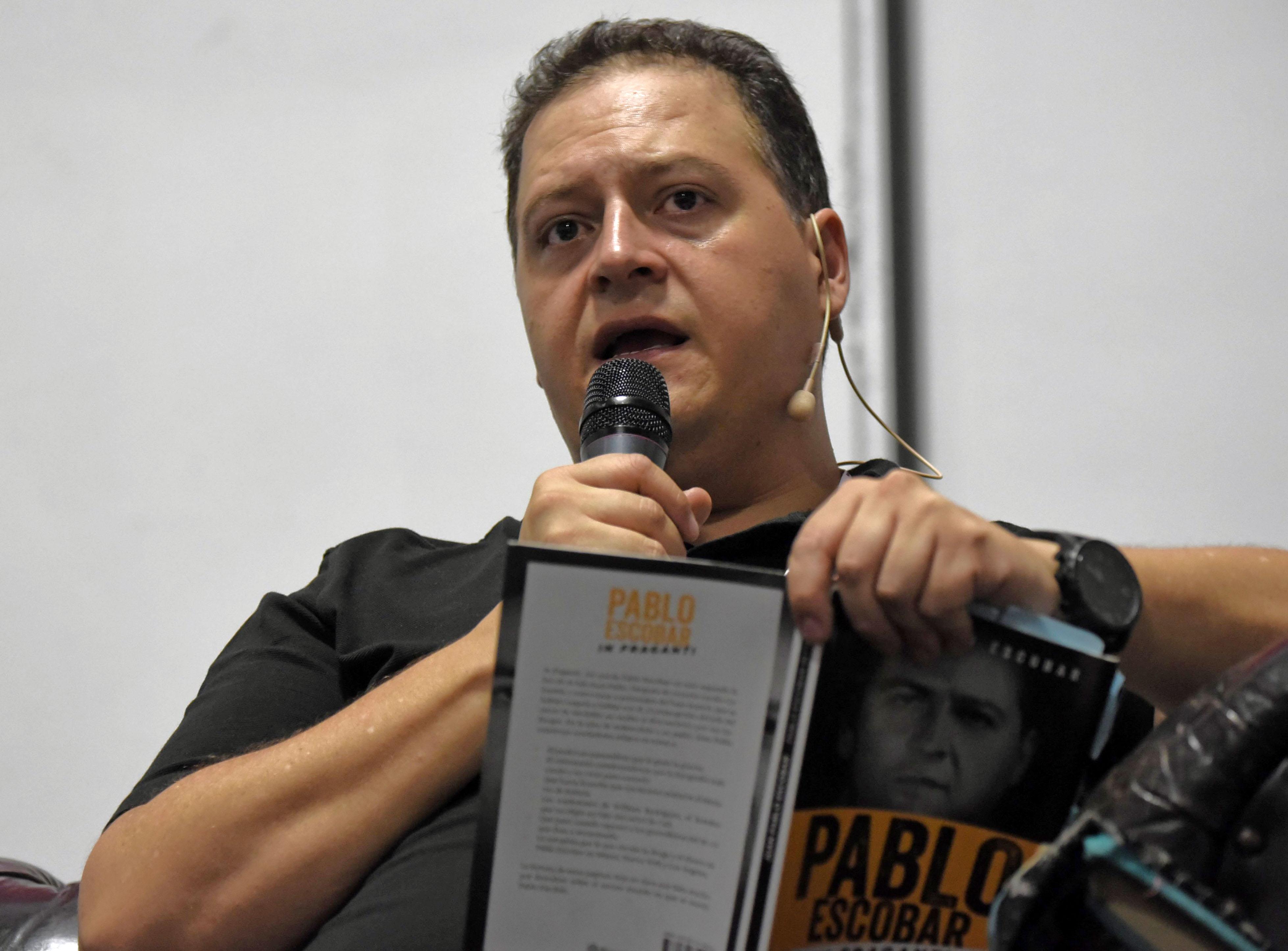 Juan Pablo Escobar Henao mientras lee el libro sobre su padre (AFP)