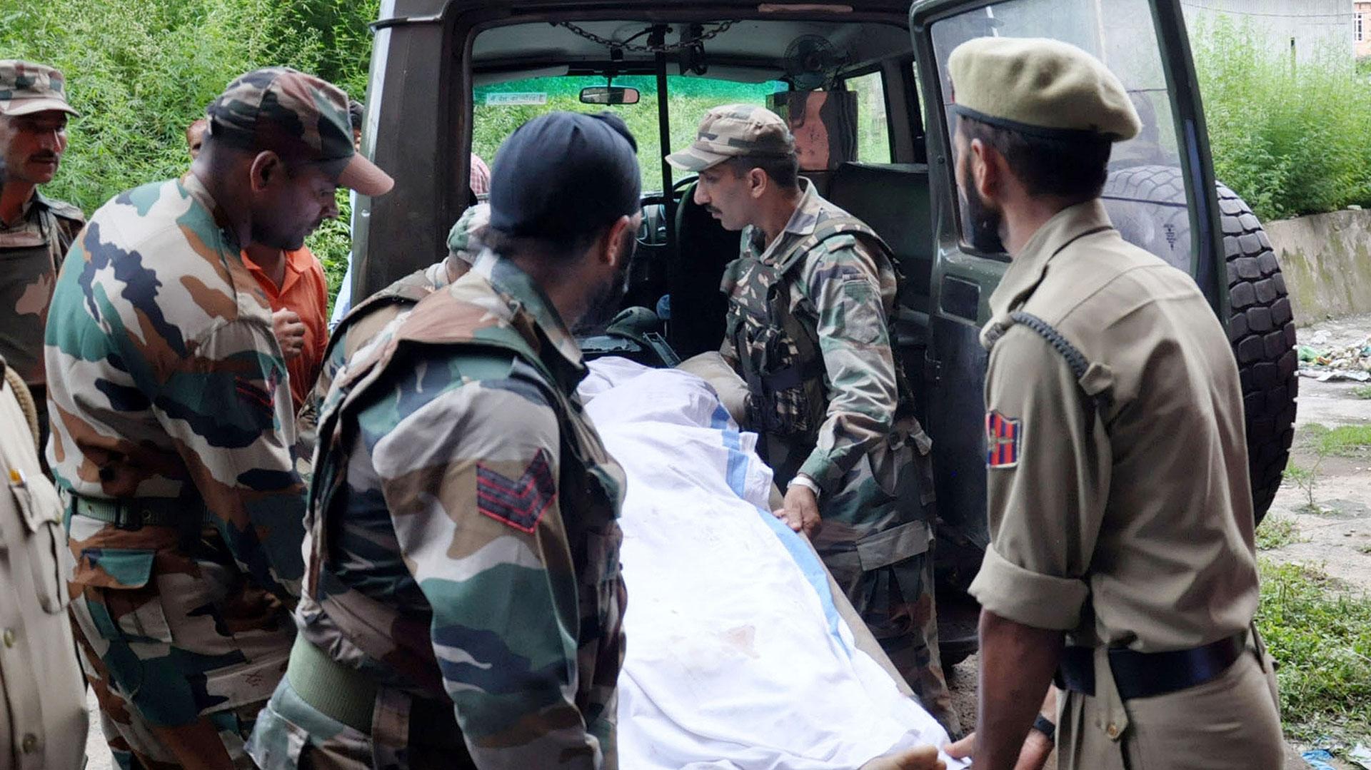 Personal del ejército indio cargan el cadáver de un soldado en un vehículo militar (AFP)