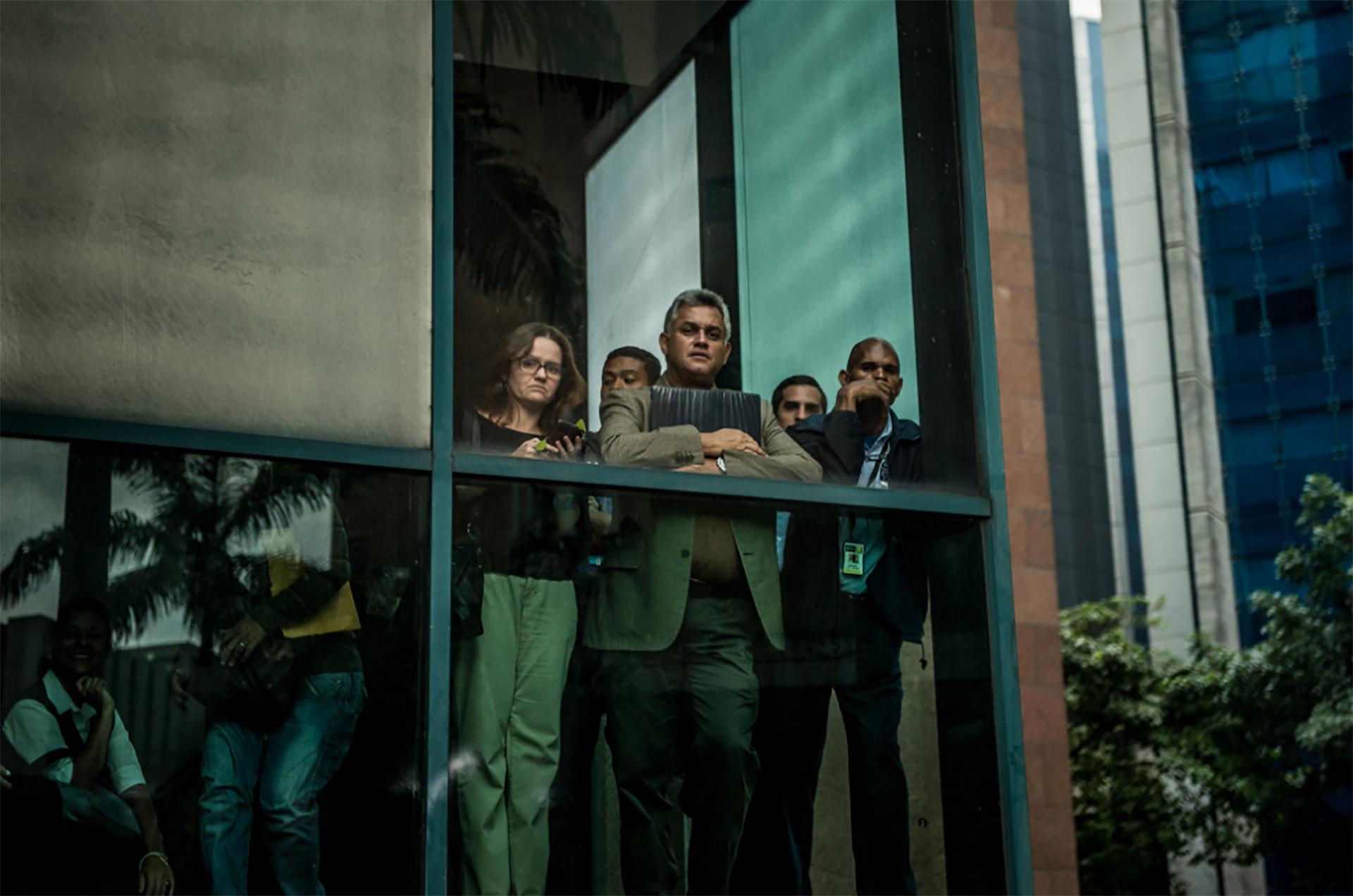 Oficinistas observan los disturbios en Caracas (Meridith Kohut for The New York Times)