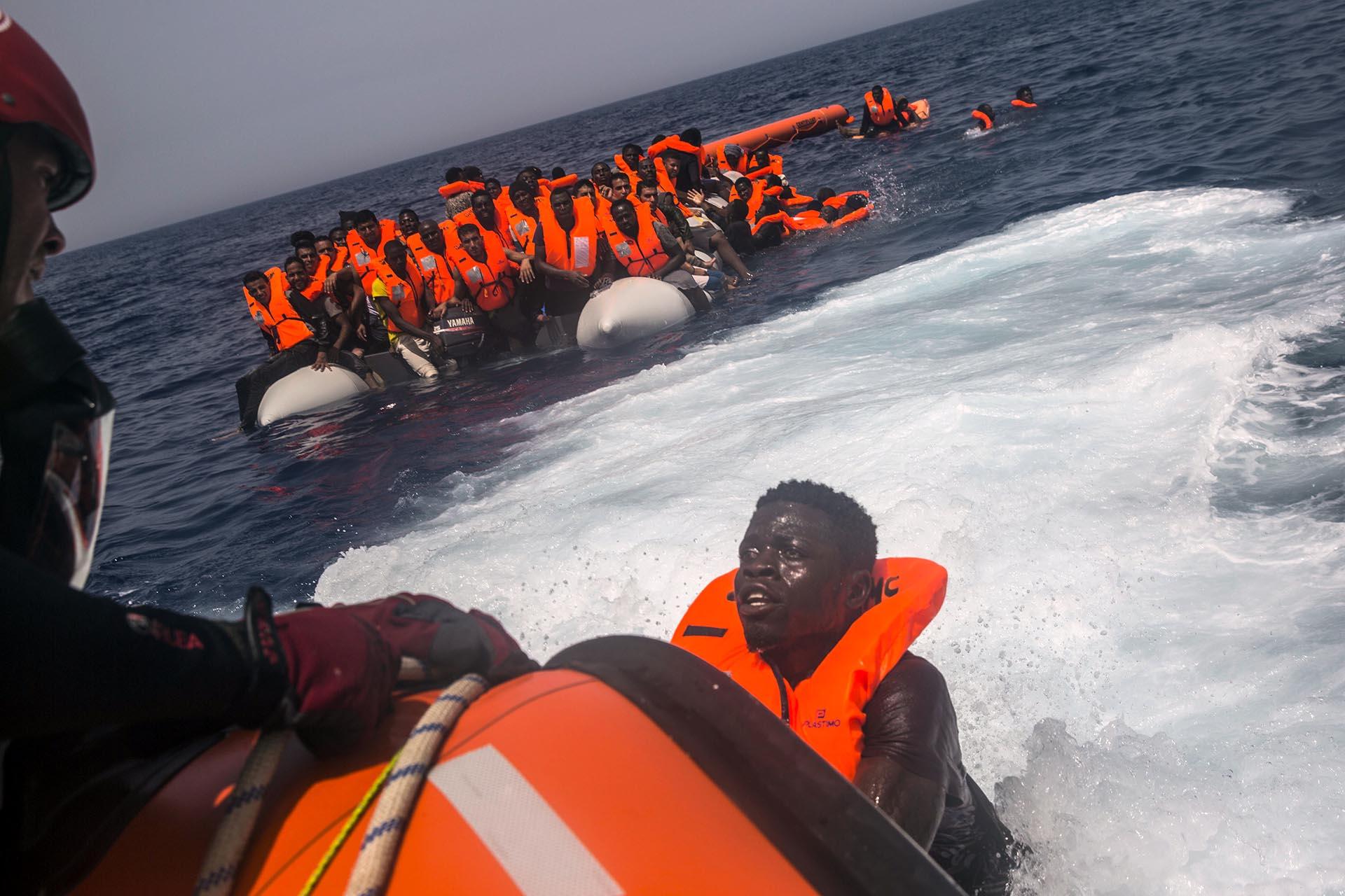 Un inmigrante africano intenta alcanzar un bote salvavidas (AP/Santi Palacios)