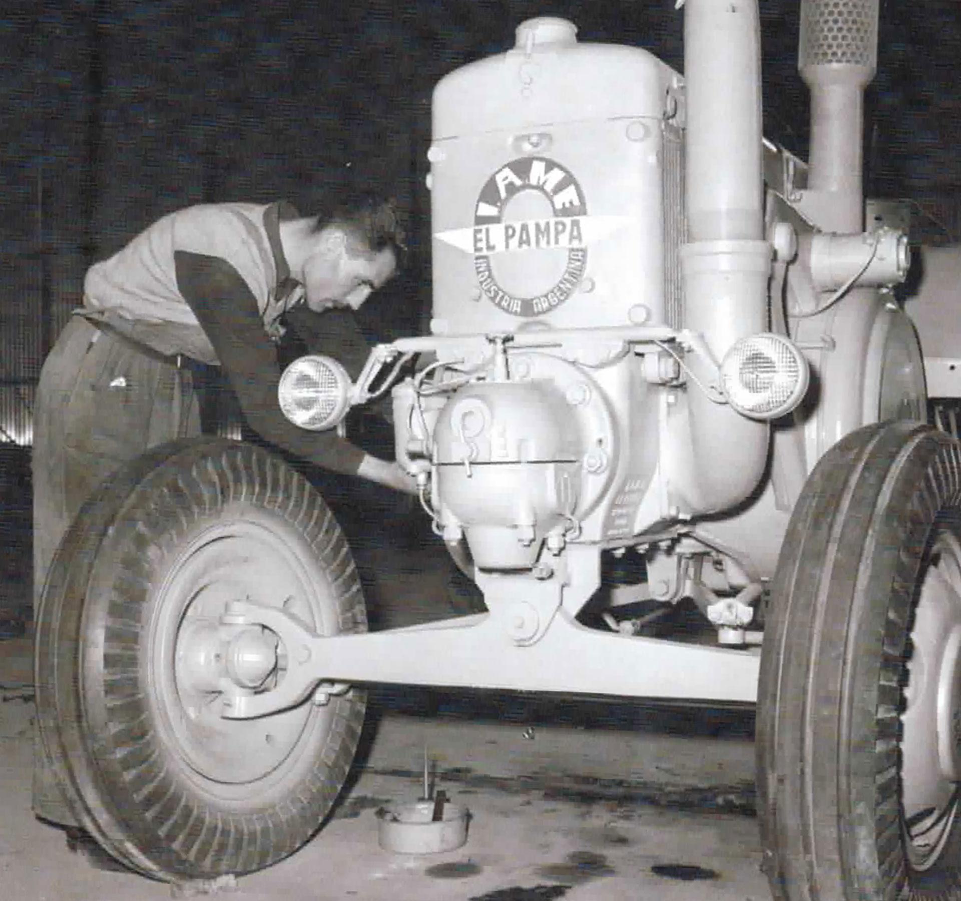 """Un obrero de IAME (Industrias Aeronáuticas y Mecánicas del Estado) trabaja sobre un tractor """"El Pampa"""""""