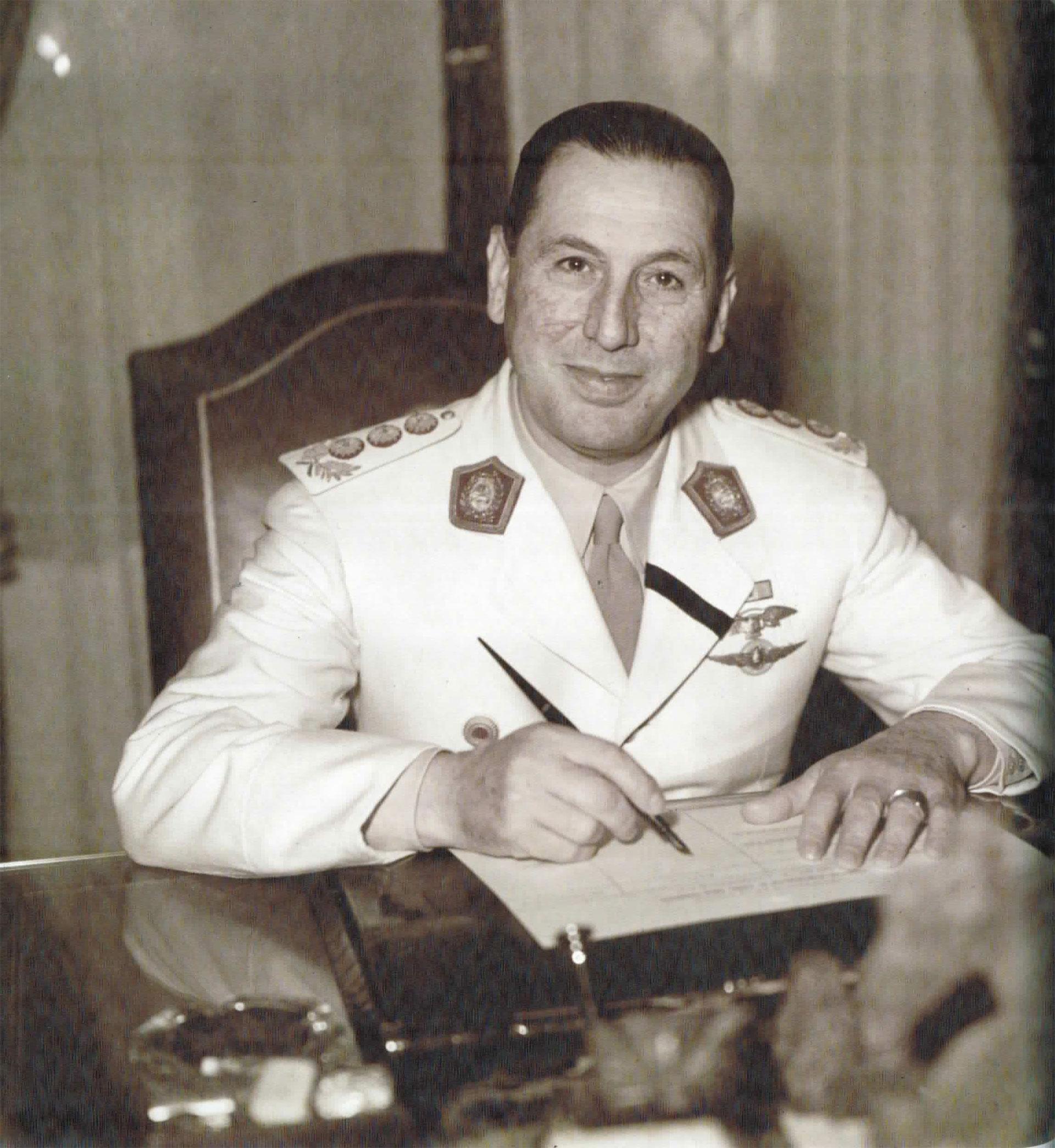 Perón posa para la cámara de Fusco, lapicera en mano. En su solapa, la banda negra cruzada que indica el luto por su esposa