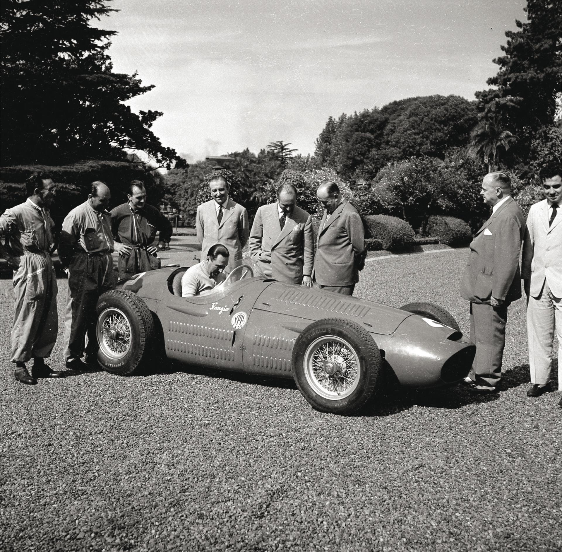 Perón al volante de la Maserati 250 f de 1954, durante una visita de Juan Manuel Fangio a la quinta de Olivos. El campeón de automovilismo está de pie a su lado.