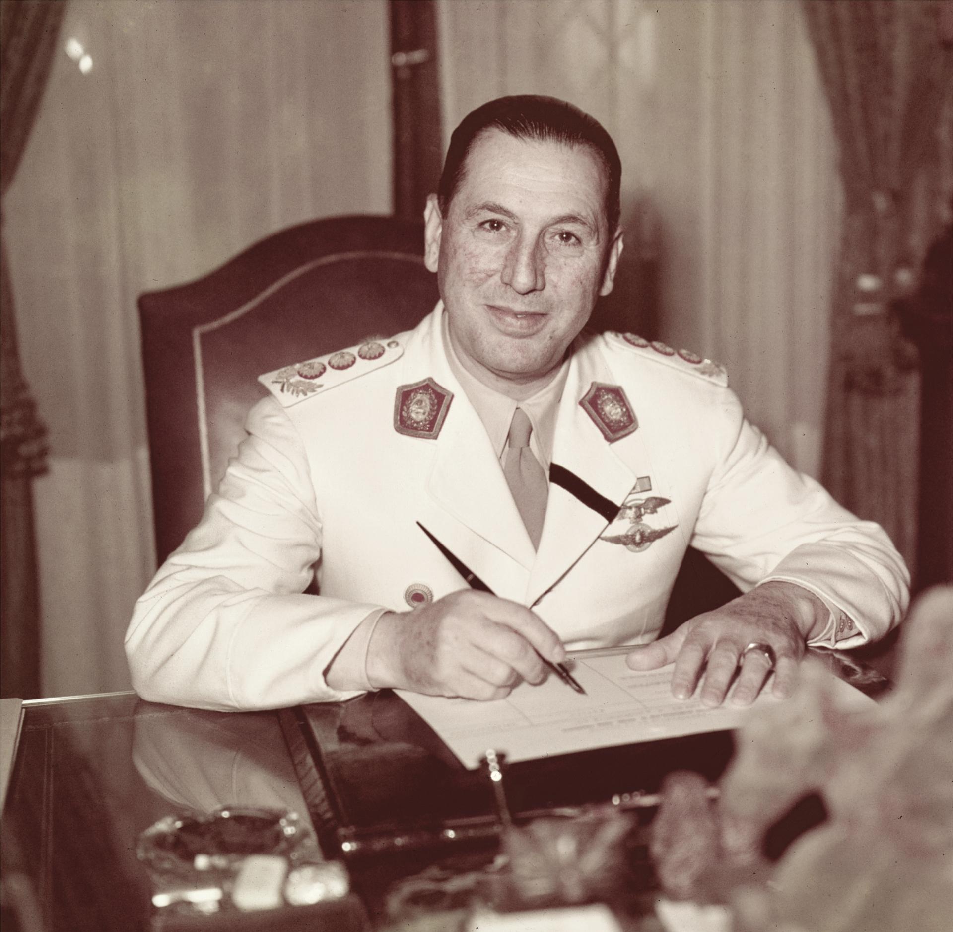 Perón posa para la cámara de Fusco, lapicera en mano. En su solapa, la banda negra cruzada que indica el luto por su esposa.