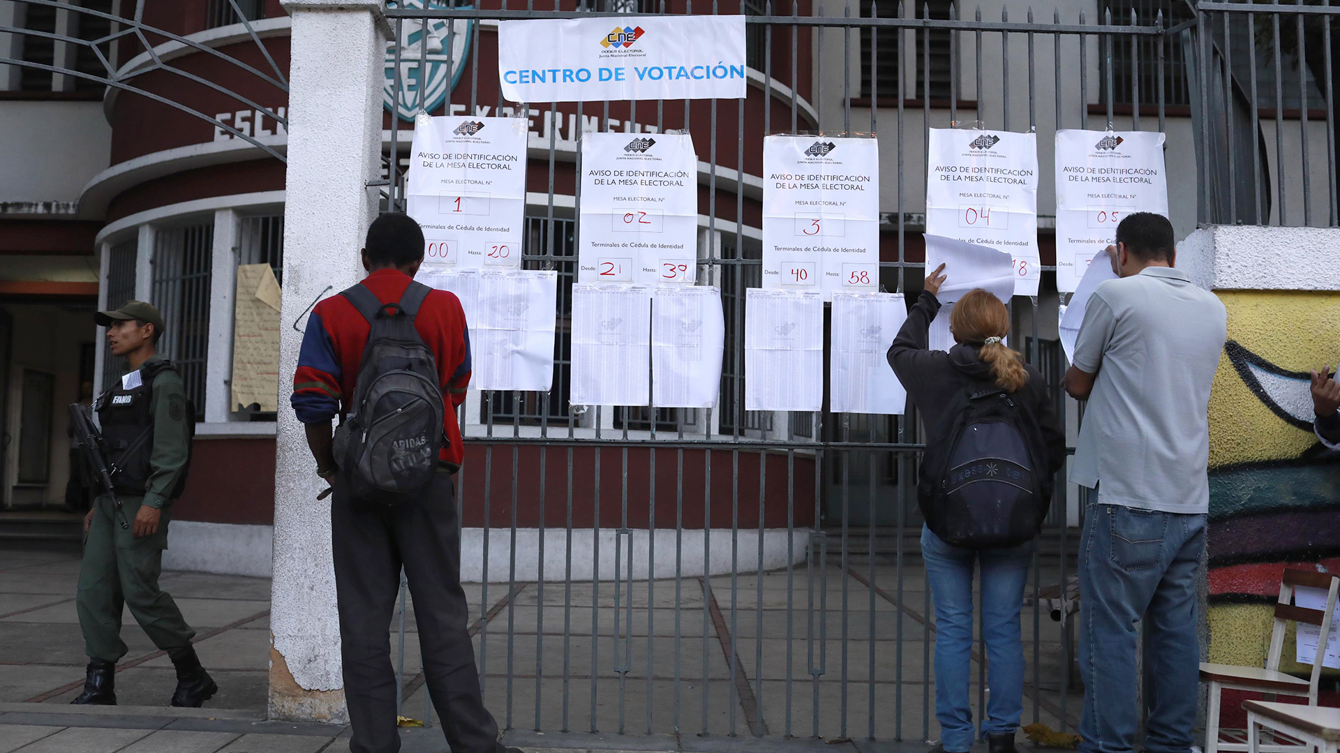 Tres personas revisan las listas antes de votar (Reuters)