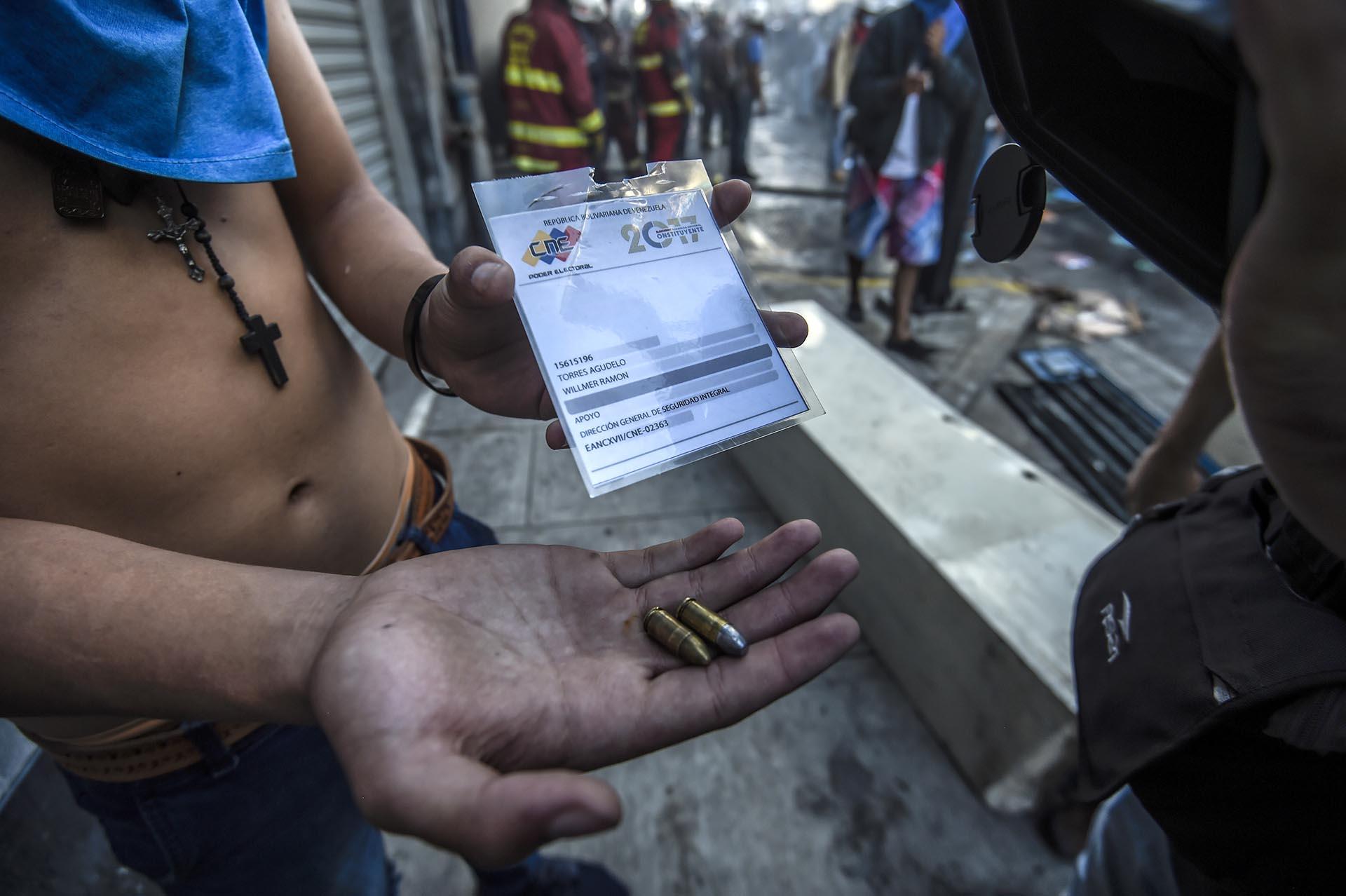 Un manifestante muestra las balas que usaron durante la jornada de votación las fuerzas represivas de Maduro (AFP)