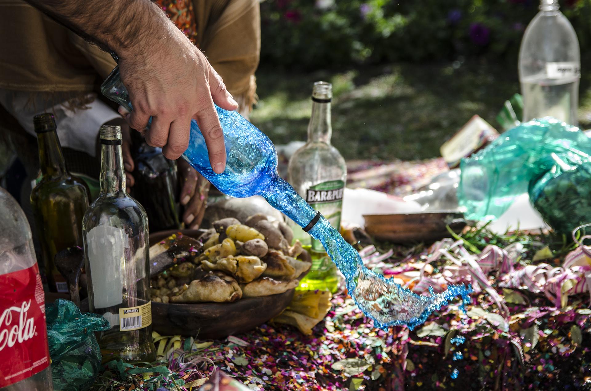 """Mediante la corpachada se """"alimenta"""" a la Pachamama. Se realiza un pozo en la tierra, donde se colocan alimentos y bebidas, que varían. Chicha, vino, comidas criollas, hojas de coca y otras ofrendas. Todo lo creado proviene de la tierra: se trata de devolverle algo de lo que da. Foto: en Jujuy se celebra en distintos puntos a lo largo de la provincia."""