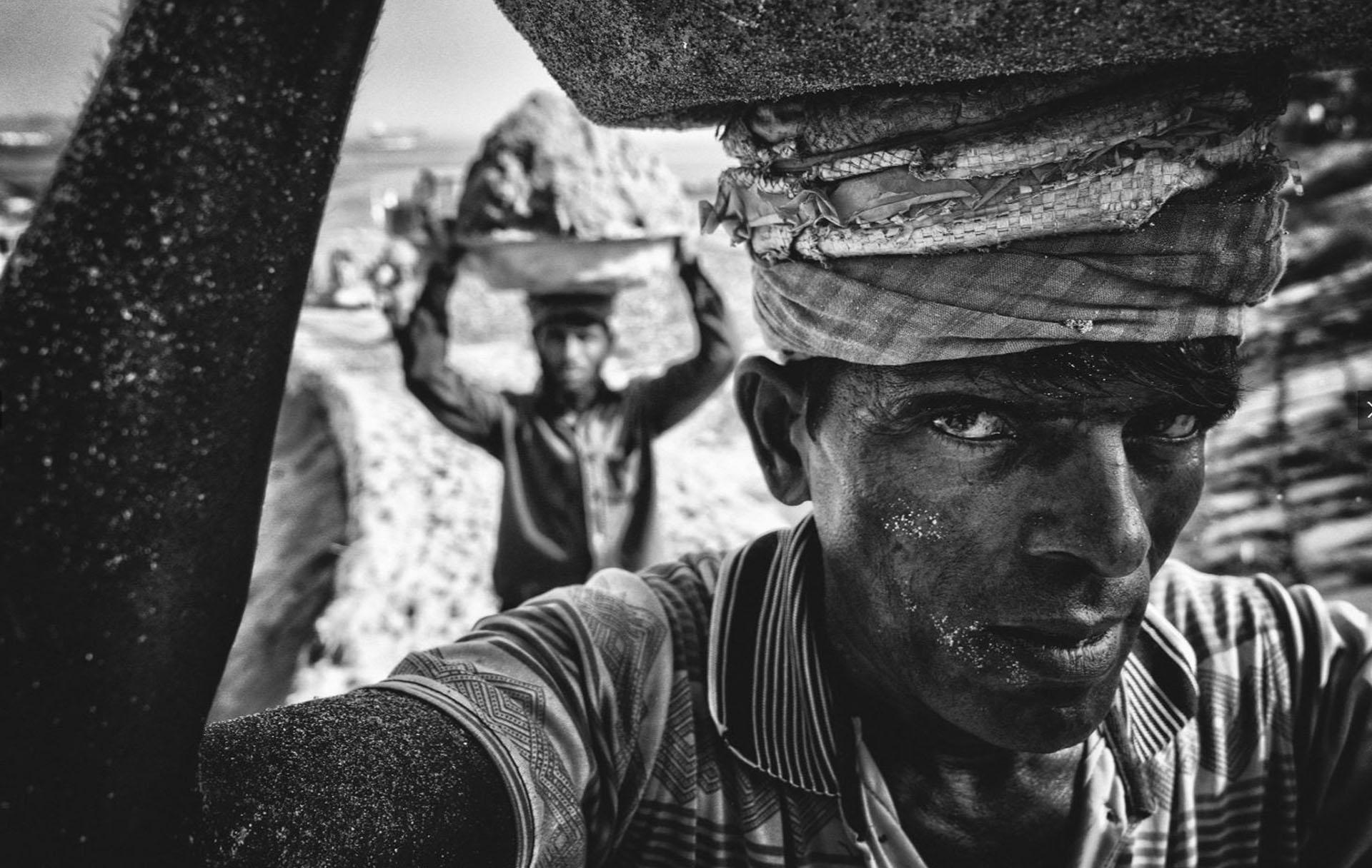 Gente – Voto propular. En Bangladesh, a la orilla del río Dhaleswari, trabajadores cargan arena para presevarla en un lugar cercano. Por Tanveer Hassan Rohan