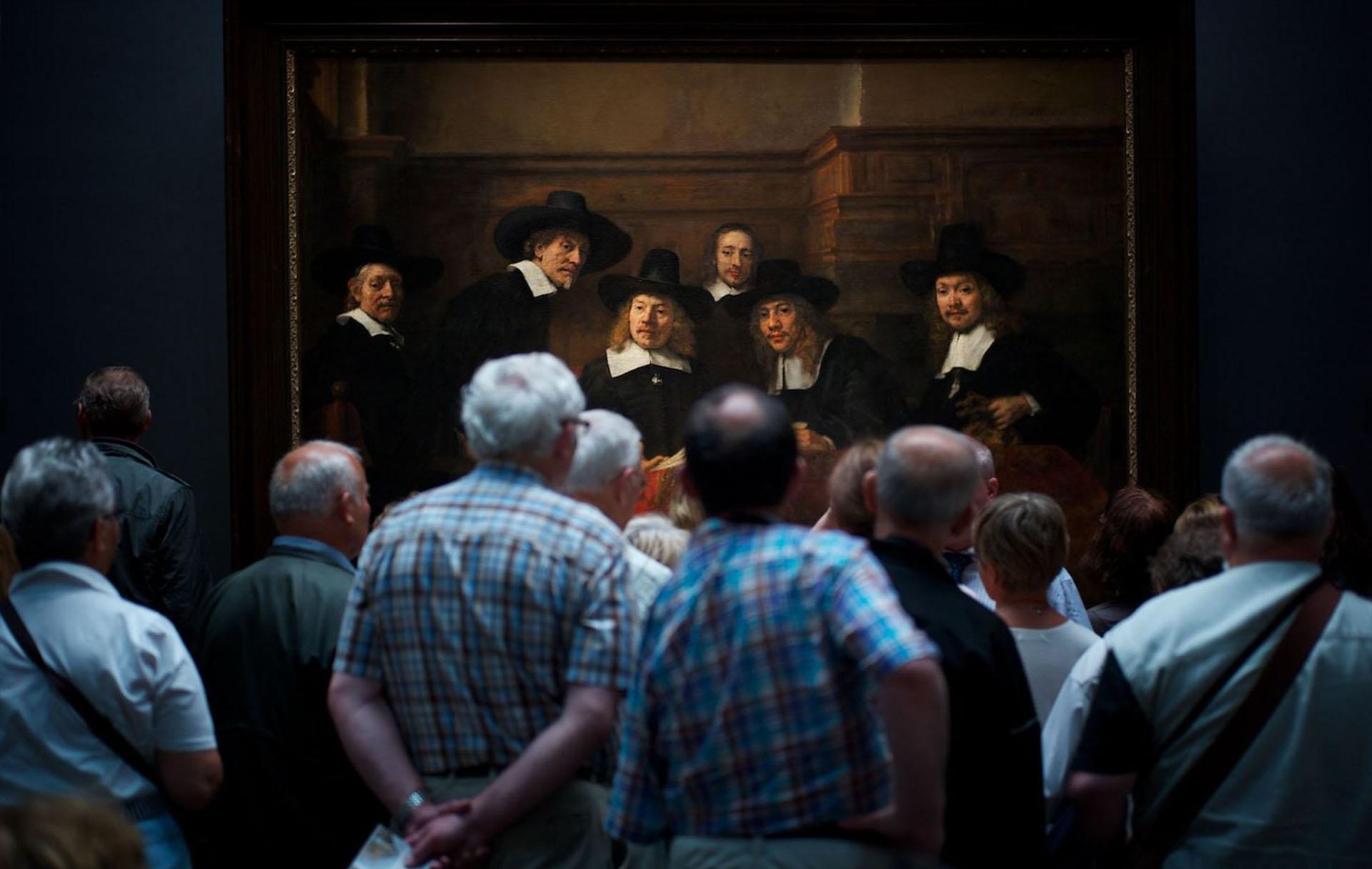 """Gente – Segundo lugar. Un grupo observa el famoso cuadro de Rembrandt Los síndicos de los pañeros, en Amsterdam. """"Me reí cuando me di cuenta que la gente en el cuadro también parece mirar con curiosidad a los vistantes"""", dijo el autor. Por Julius Y."""