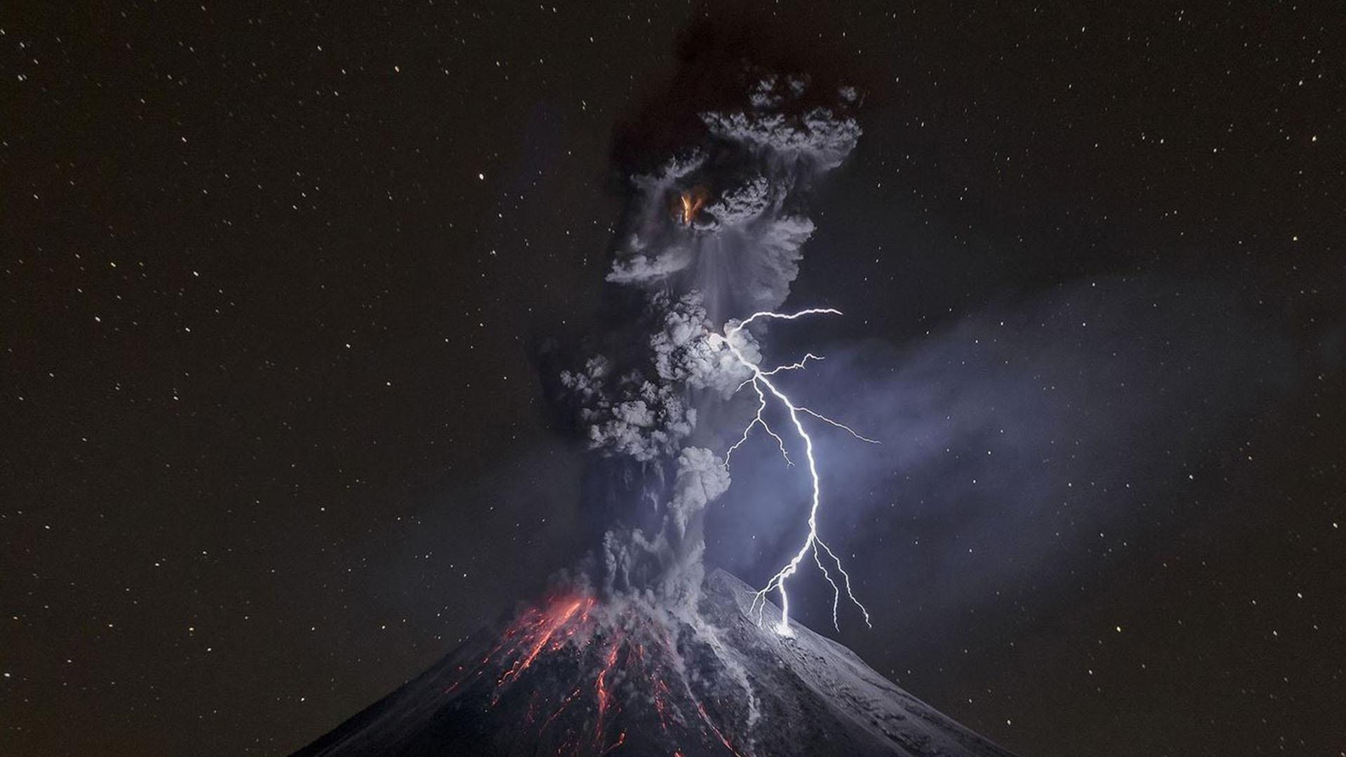 """Naturaleza – Primer lugar. Una impresionante toma del volcán de Colima. """"estaba en Comala cuando de repente vi una incandescencia y el cráter comenzó a disparar. Segundos después, una poderosa explosión volcánica expulsó una nube de cenizas y un rayo iluminó la escena. Fue uno de los momentos más emocionantes de mi vida"""". Por Sergio Tapiro Velasco"""