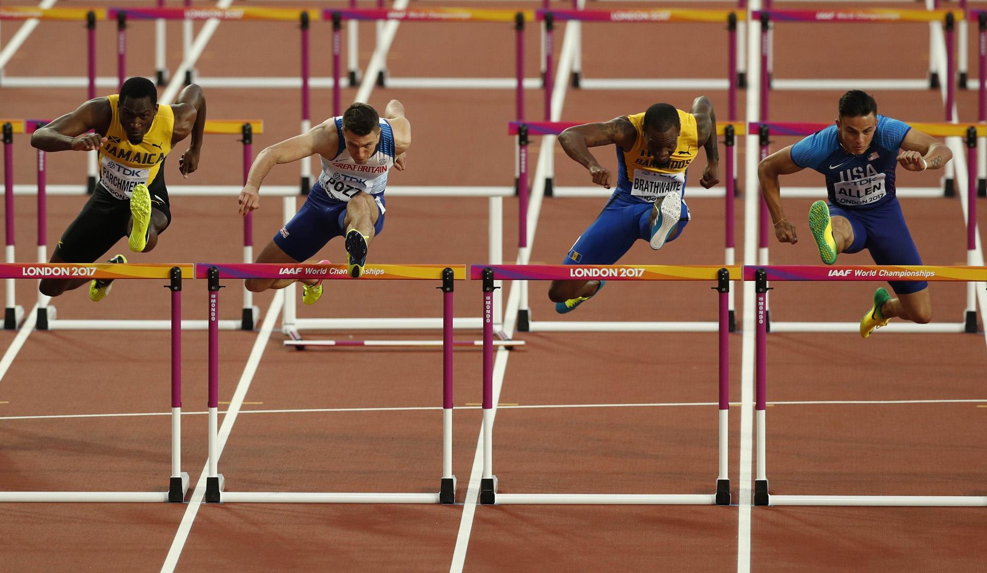 Los atletas saltan hacia la meta en la semifinal de los 110 metros con vallas