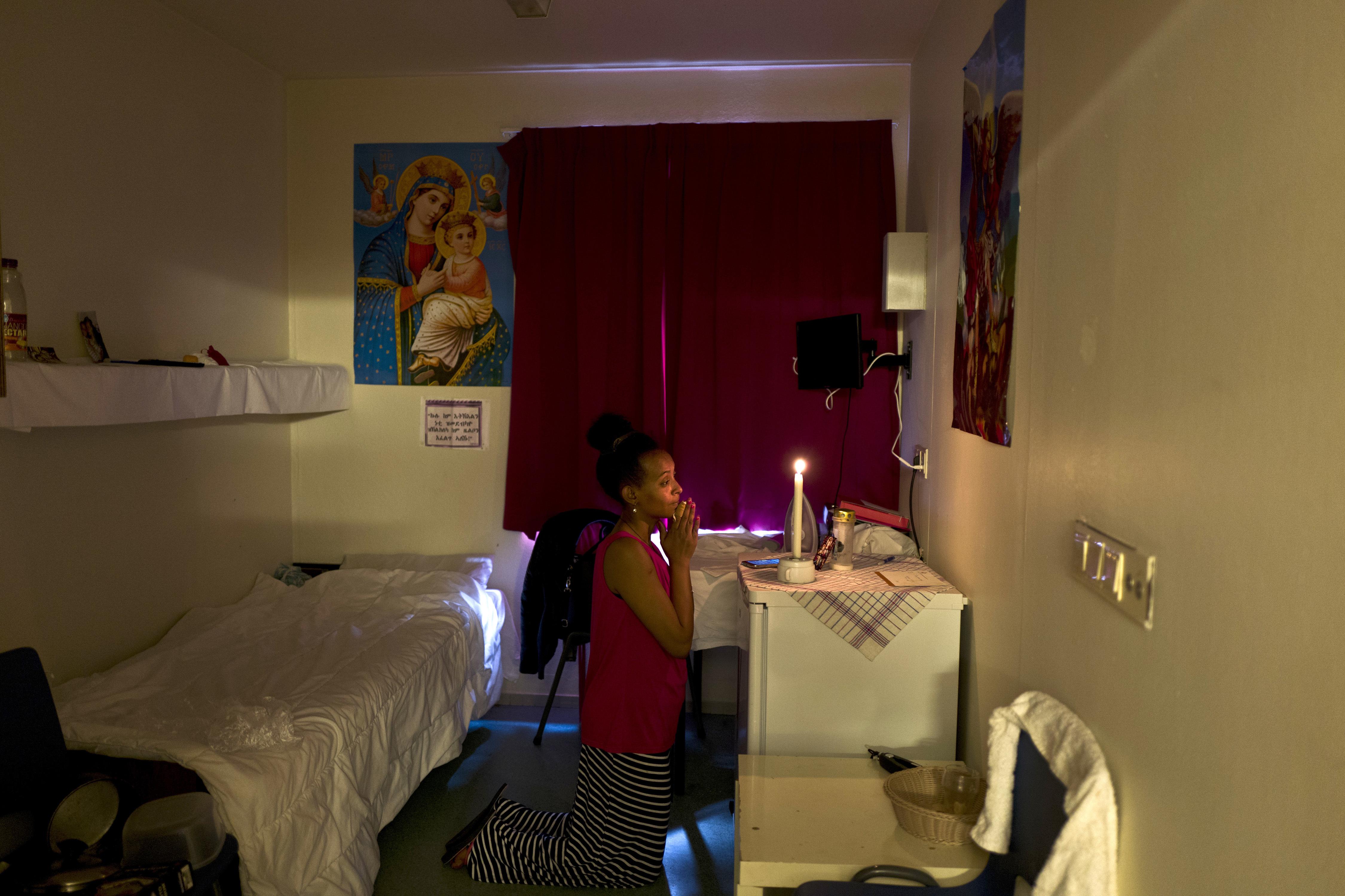 Meza Negadtu, una inmigrante de 29 años de Eritrea, reza en su habitación(AP Photo/Muhammed Muheisen)