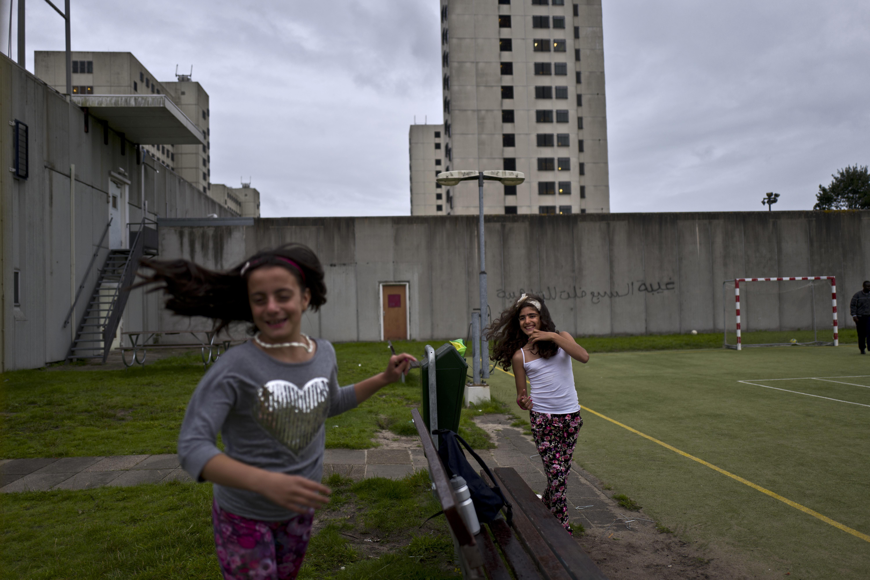Las niñas sirias Mishleen Samir, de 10 años,y su amiga Claire Alzain, juegan en el campo de la ex cárcel deBijlmerbajes en Amsterdam (AP Photo/Muhammed Muheisen)