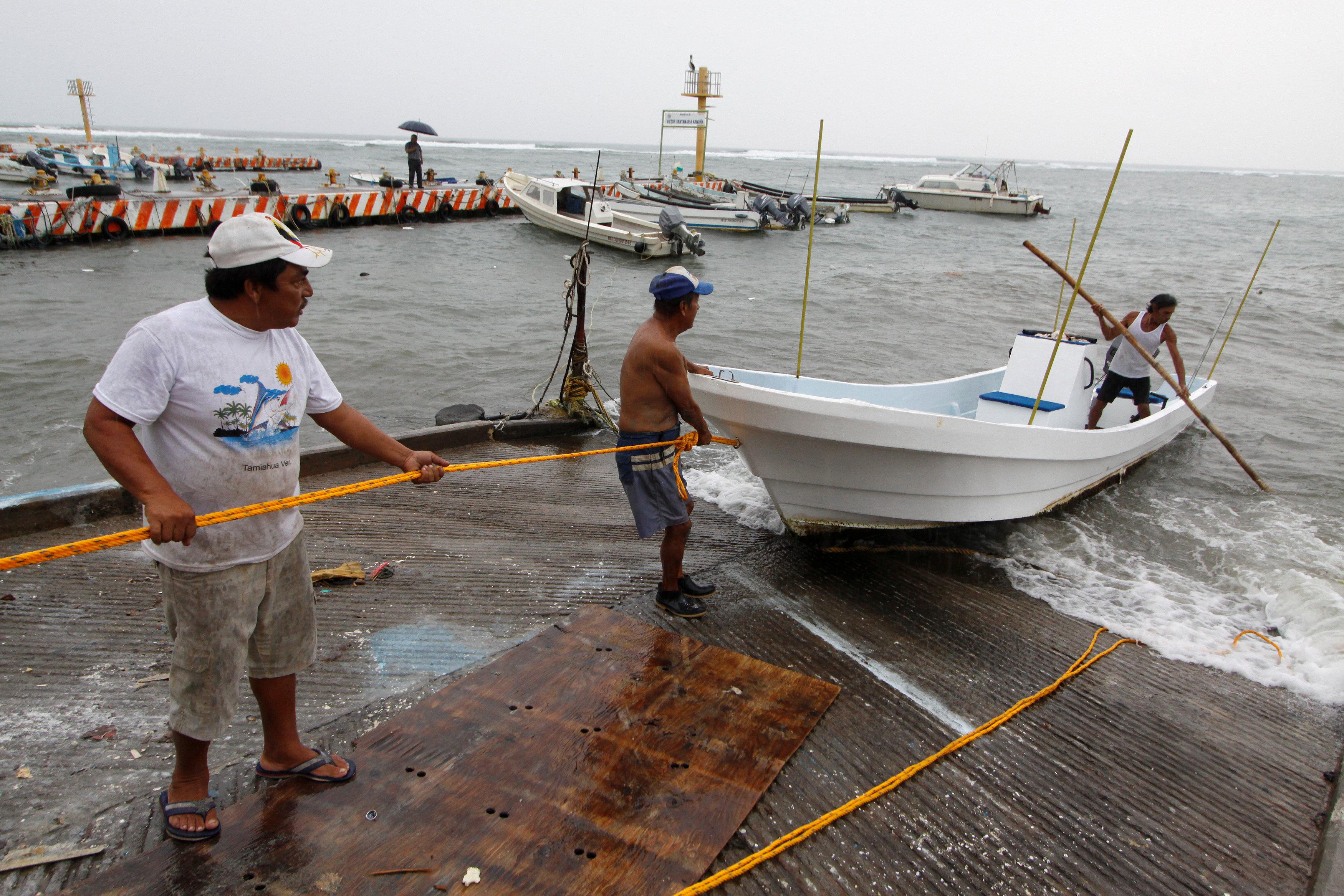 Un grupo de pescadores sacan un bote del mar en Veracruz(REUTERS/Victor Yanez)