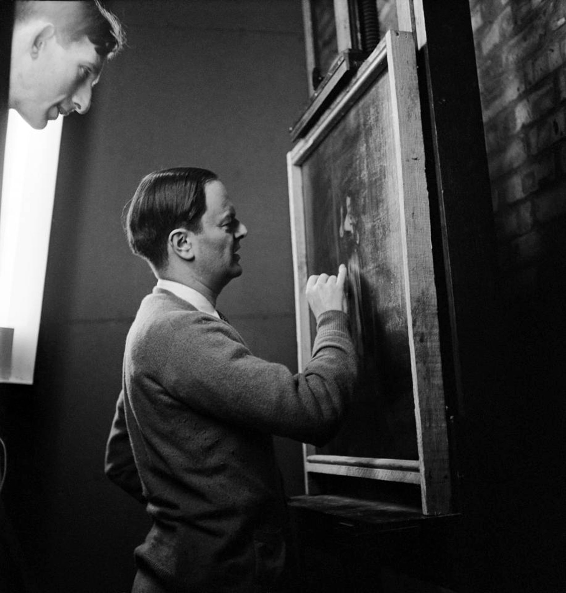 Sir Kenneth Clark, director de la National Gallery, inspecciona una obra