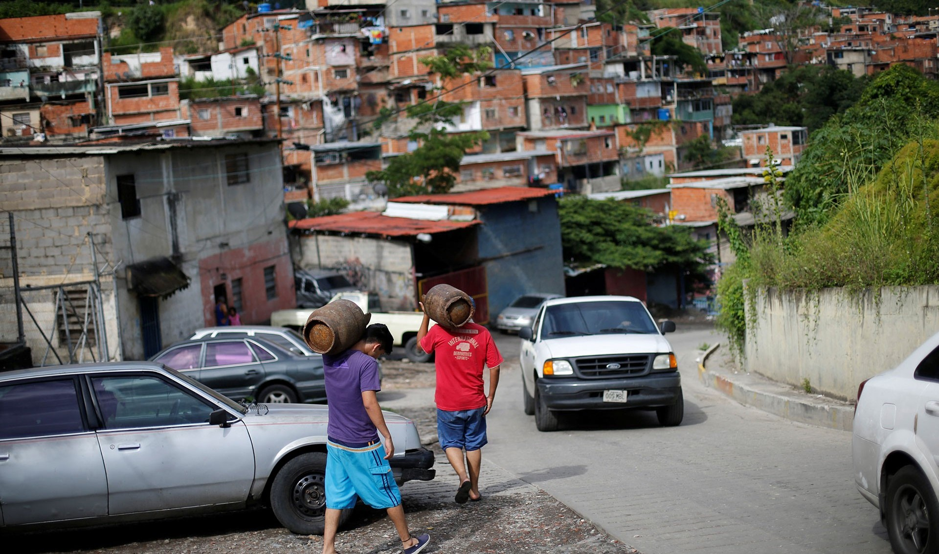 Venezolanos cargas garrafas de gas en Caracas (Reuters)