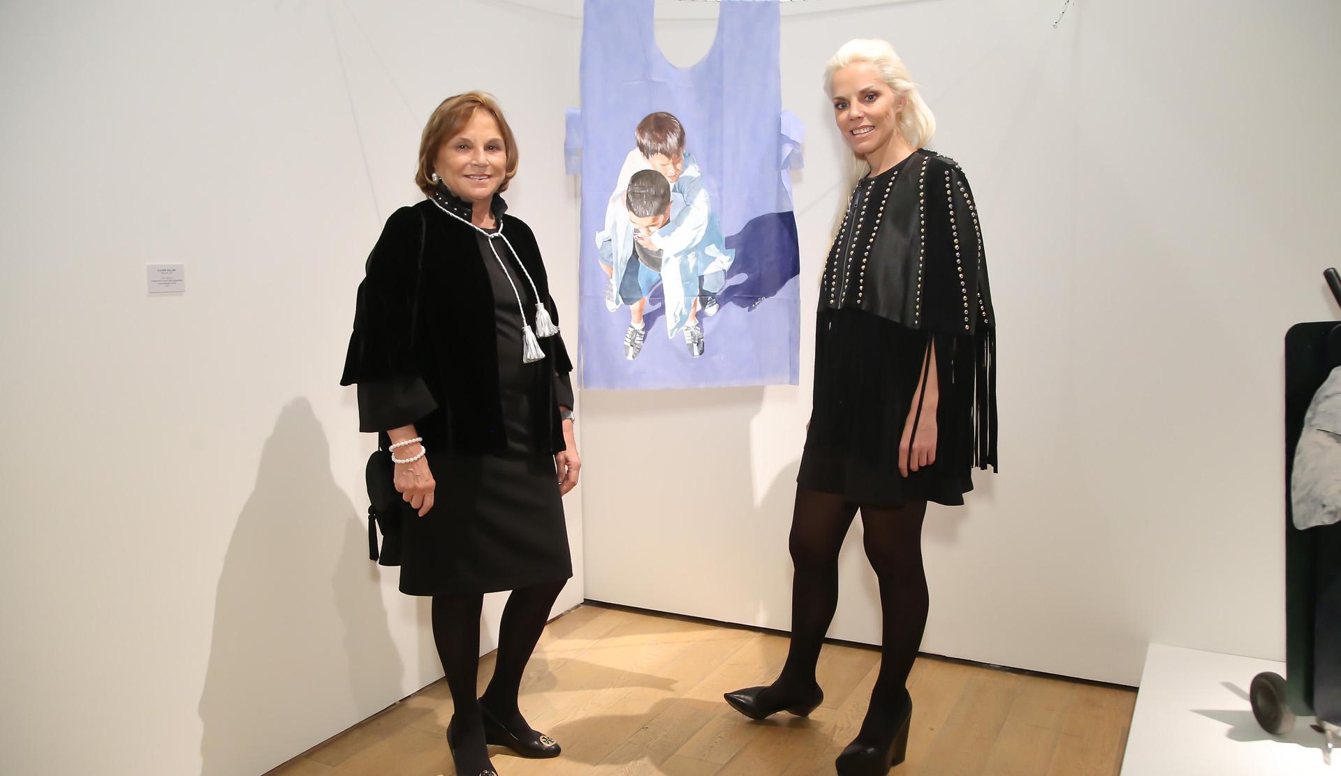 Eugenia Cerdá de Rossi y Agustina Rossi, presidente y directora de Fundación Rossi respectivamente, junto a la obra de Claudio Gallina, que propone que las batas azules descartables salgan del gabinete y entren en un museo