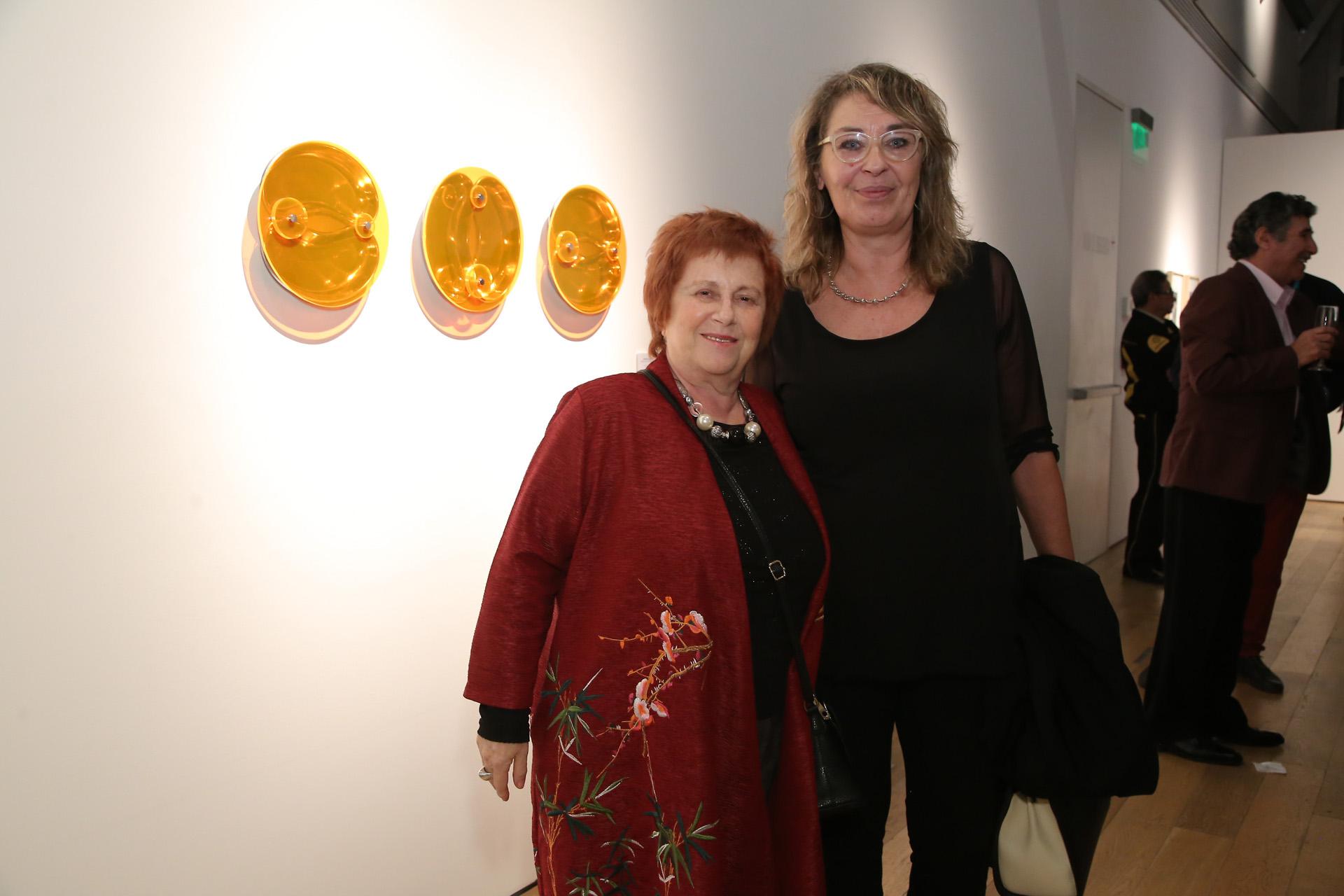 Las artistas plásticas Dora Isdatne y Cristina Tomsig junto a su obra, en la que incorporaron a su lenguaje escultórico las bandejas de acero inoxidable empleadas en el descarte de jeringas