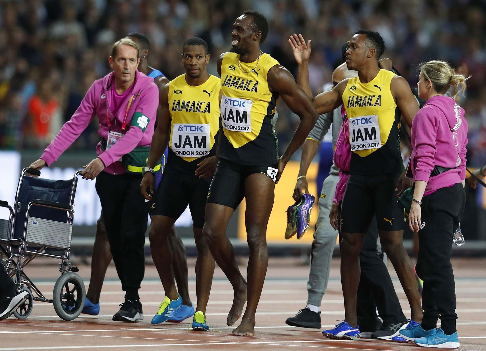Ya sin zapatillas, Bolt se retira al vestuario acompañado por los médicos y el equipo