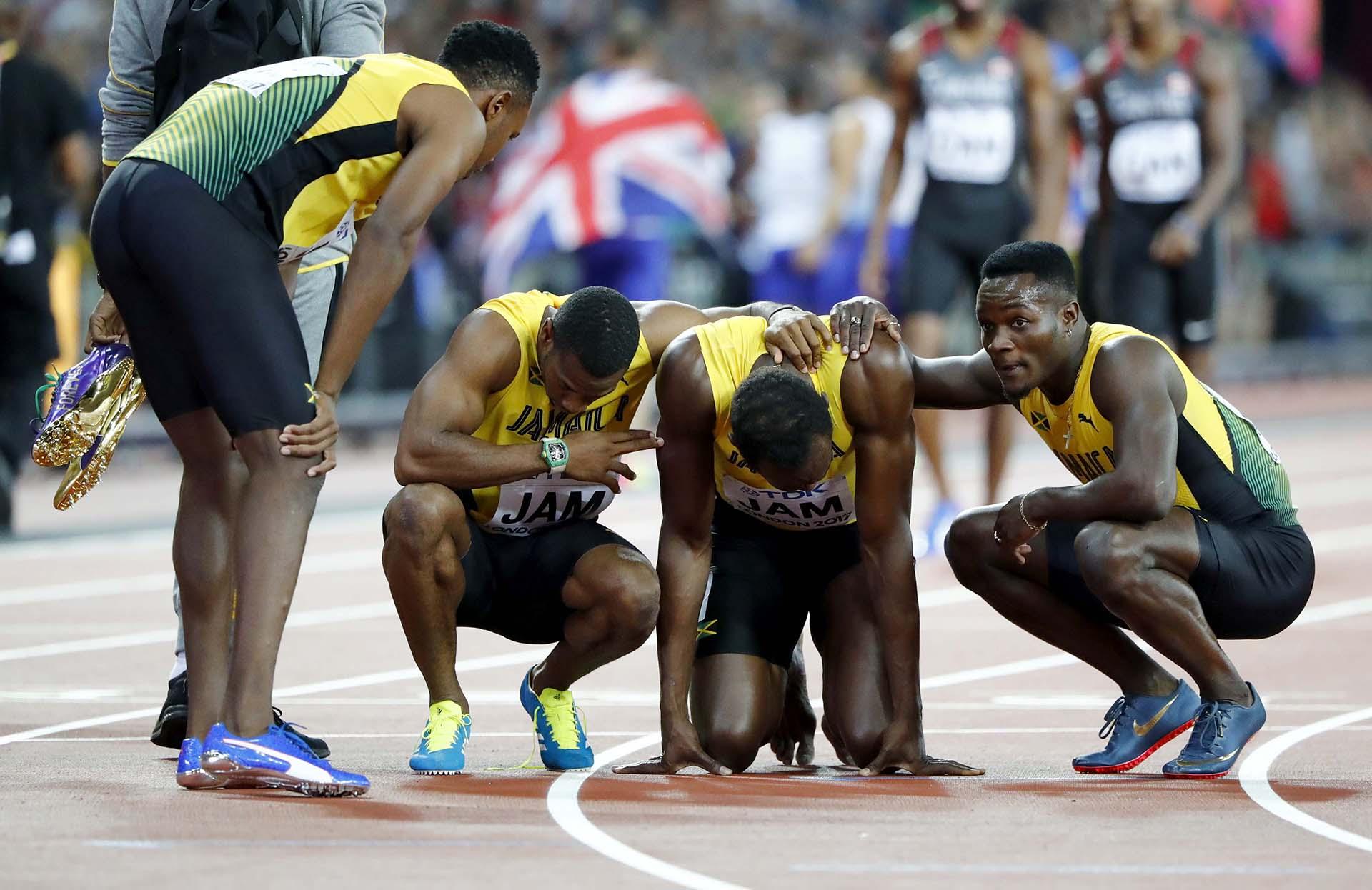 El equipo 4×100 de Jamaica al lado de la leyenda, mientras el resto celebra
